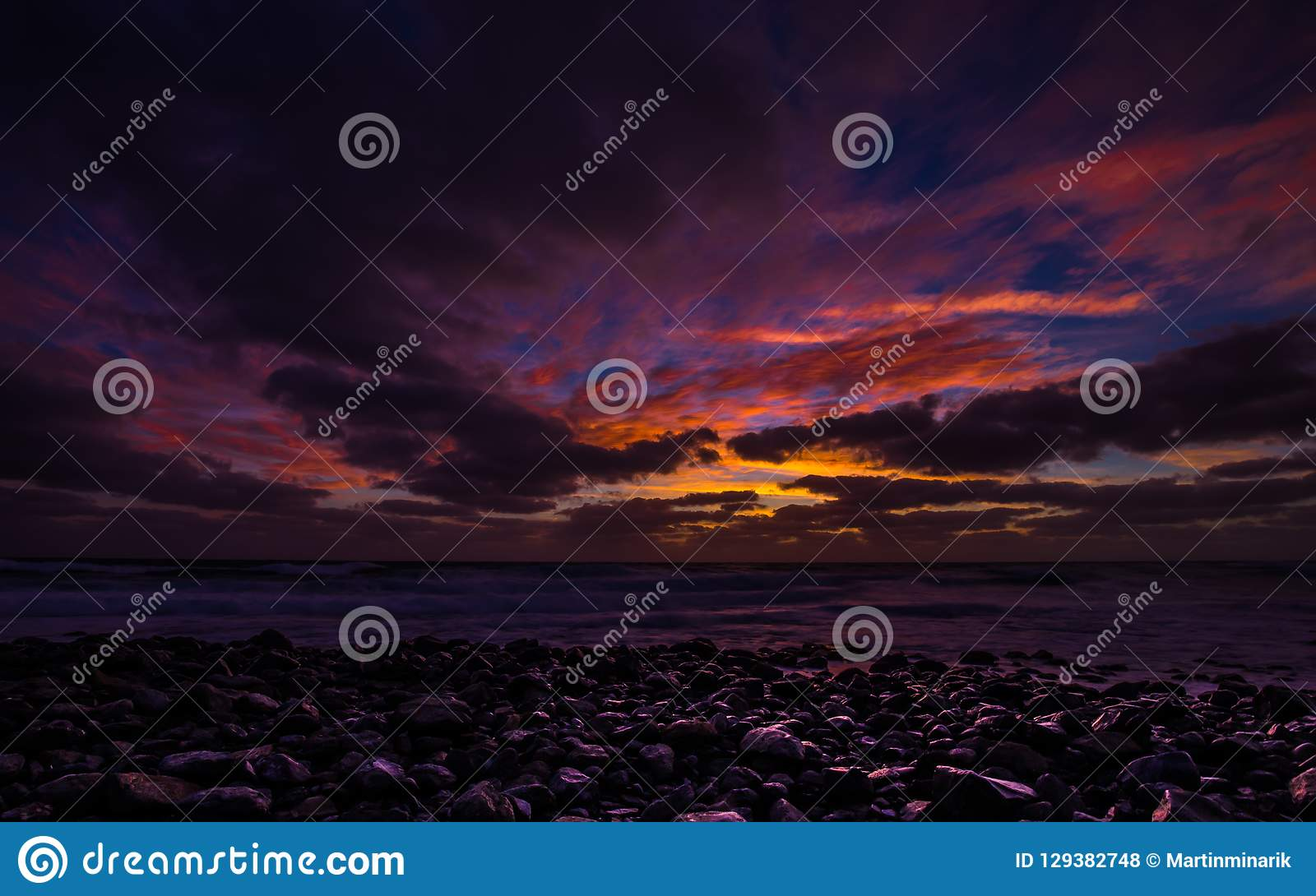 Sunrise on Praia de Igrejinh with dramatic colorful sky and rock on island of Sal