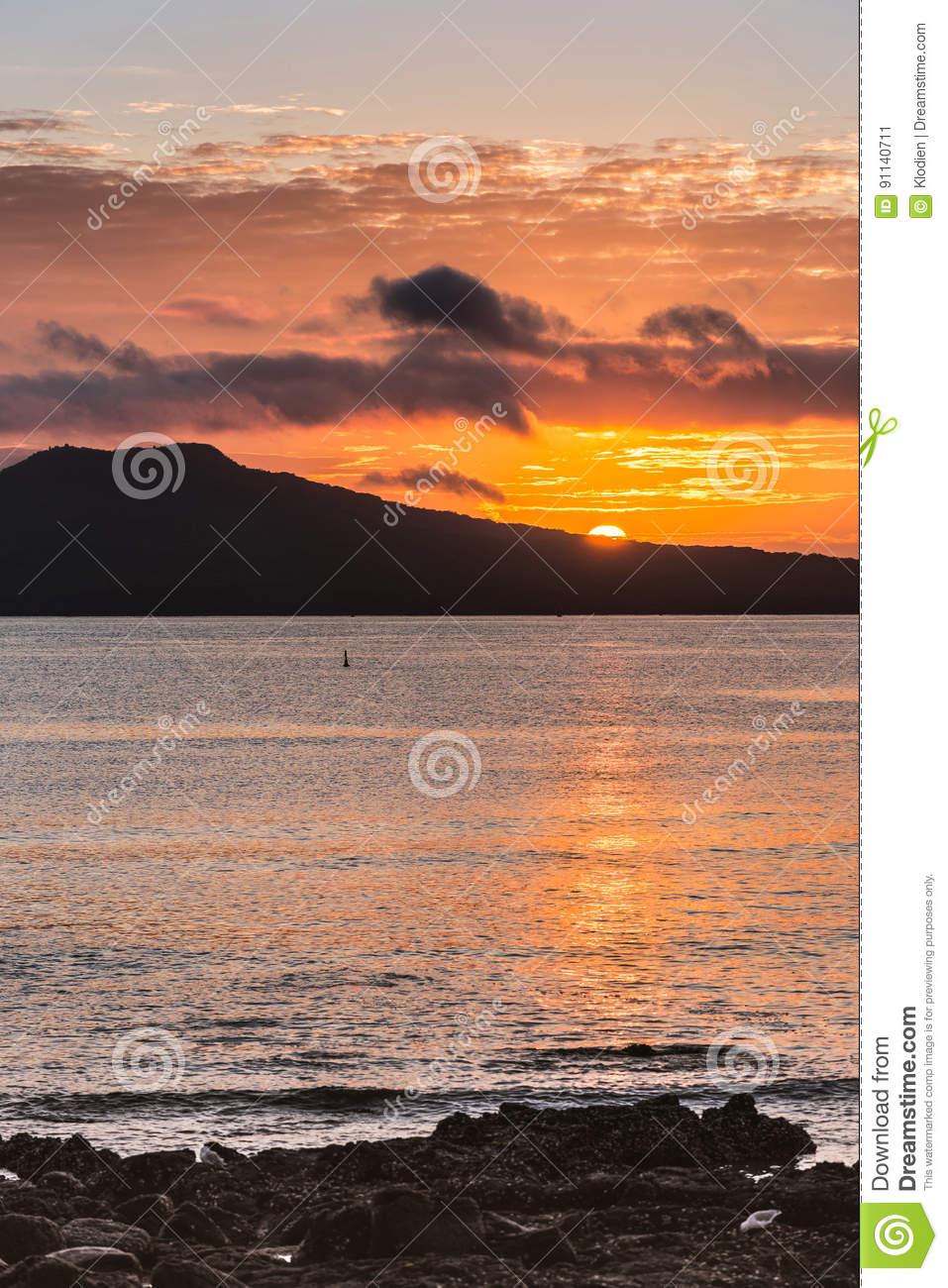 Sunrise shows half sun over Rangitoto Volcano near Auckland.