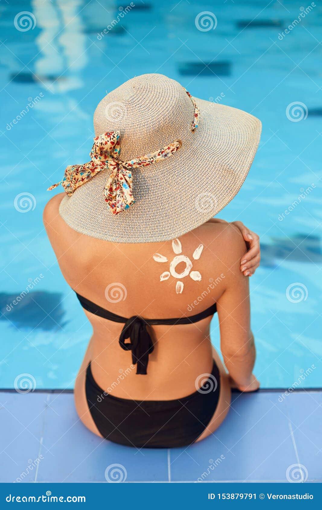 Sunscreen sunblock Γυναίκα που βάζει την ηλιακή κρέμα στον ώμο υπαίθρια από τη λίμνη κάτω από την ηλιοφάνεια την όμορφη θερινή ημ