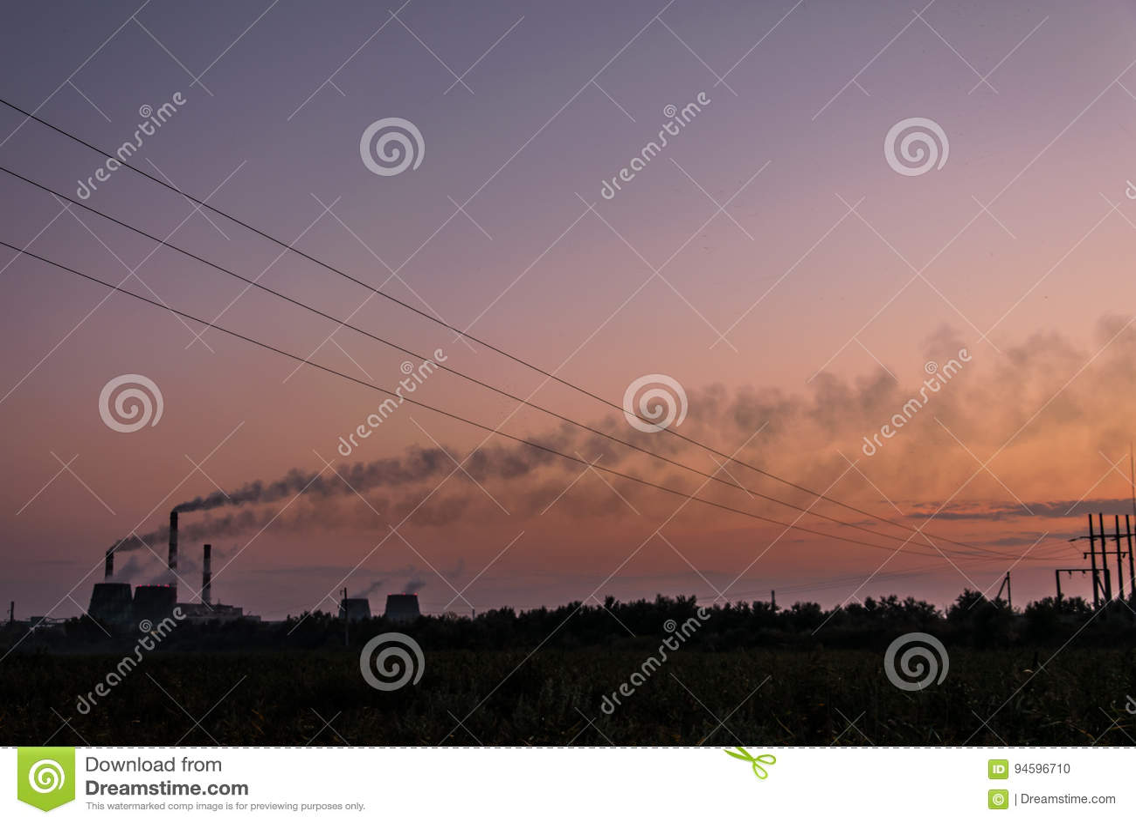 Sunset against the background of smoking chimneys
