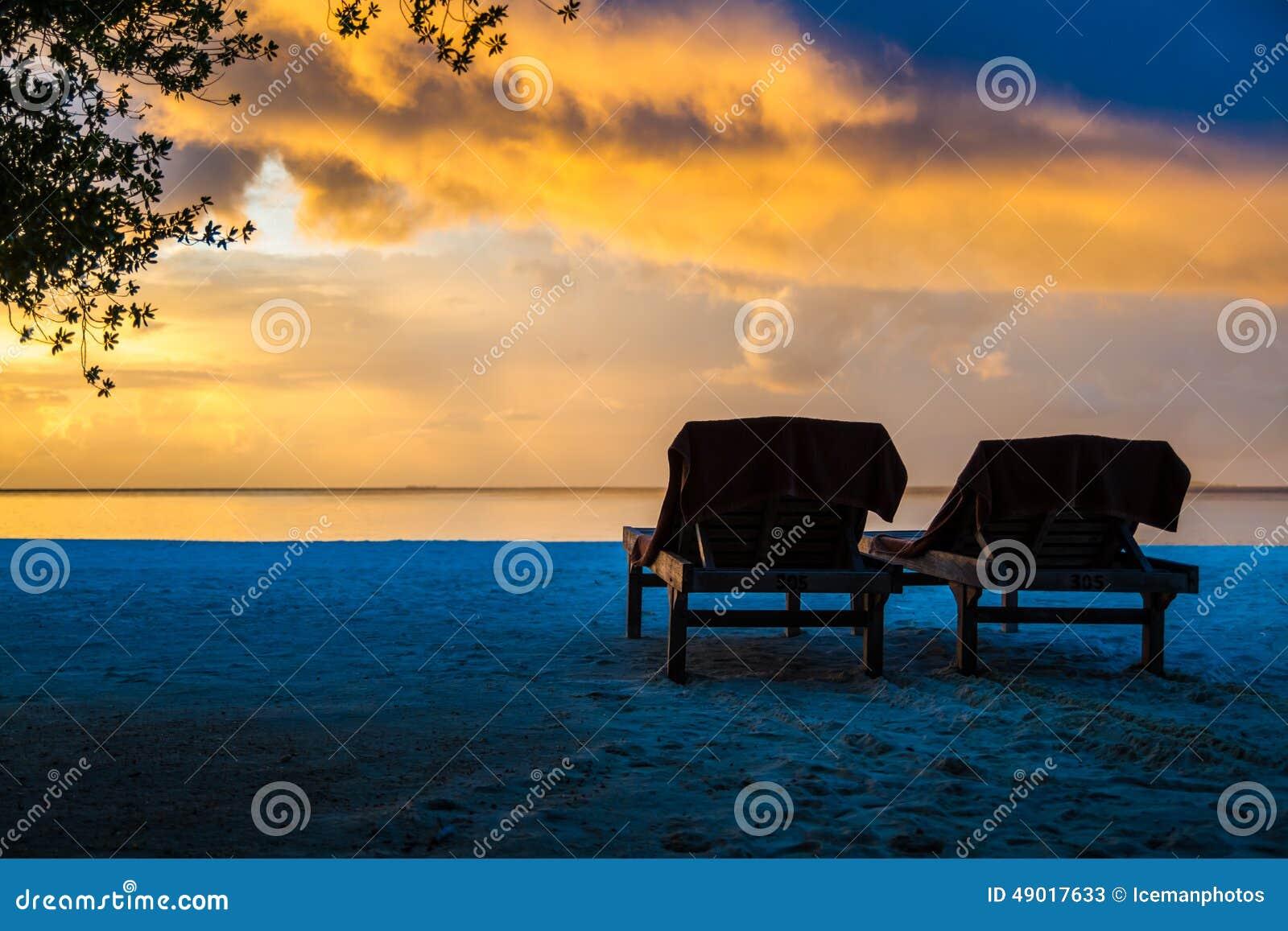 Sunset beach landscape with sunbeds, Maldives