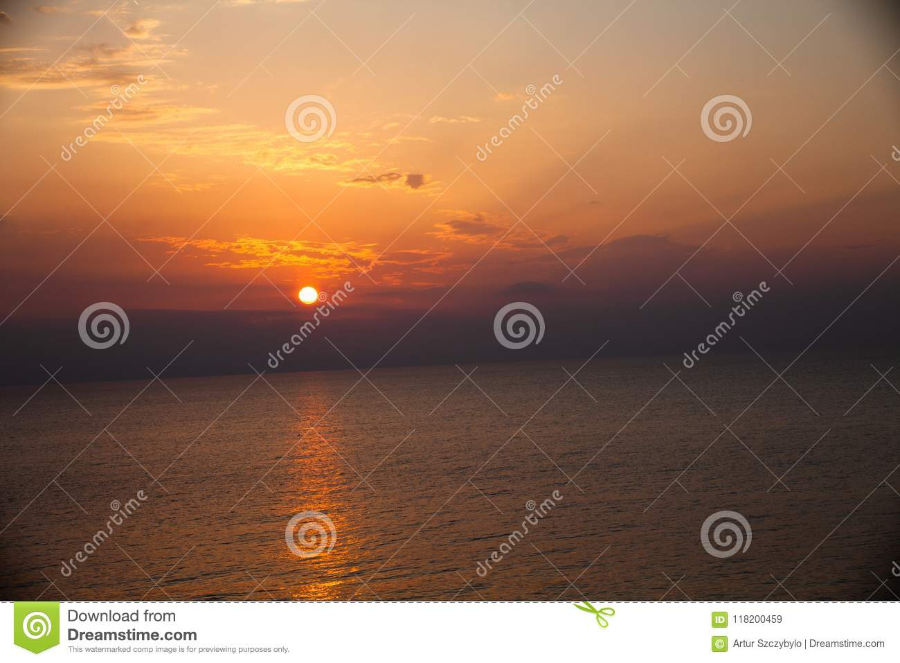 Sunset at the beach with some clouds in the sky. Blue and pink shades with dark clouds. Quiet place. Relaxing scene of beaches. Be