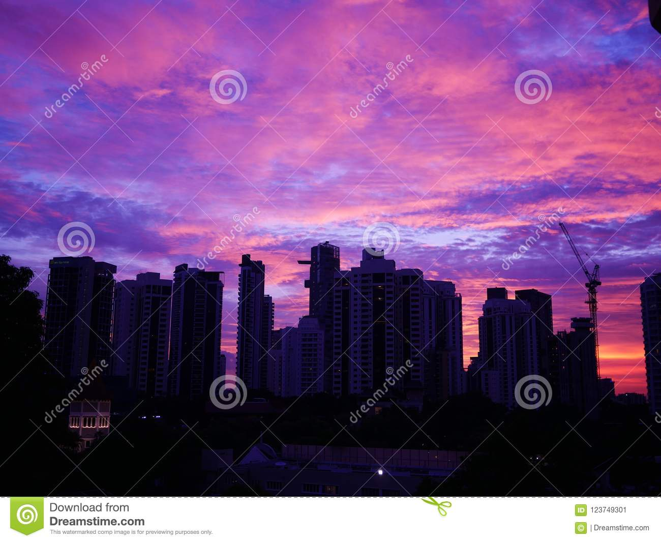 Sunset behind buildings with beautiful cloudy sky
