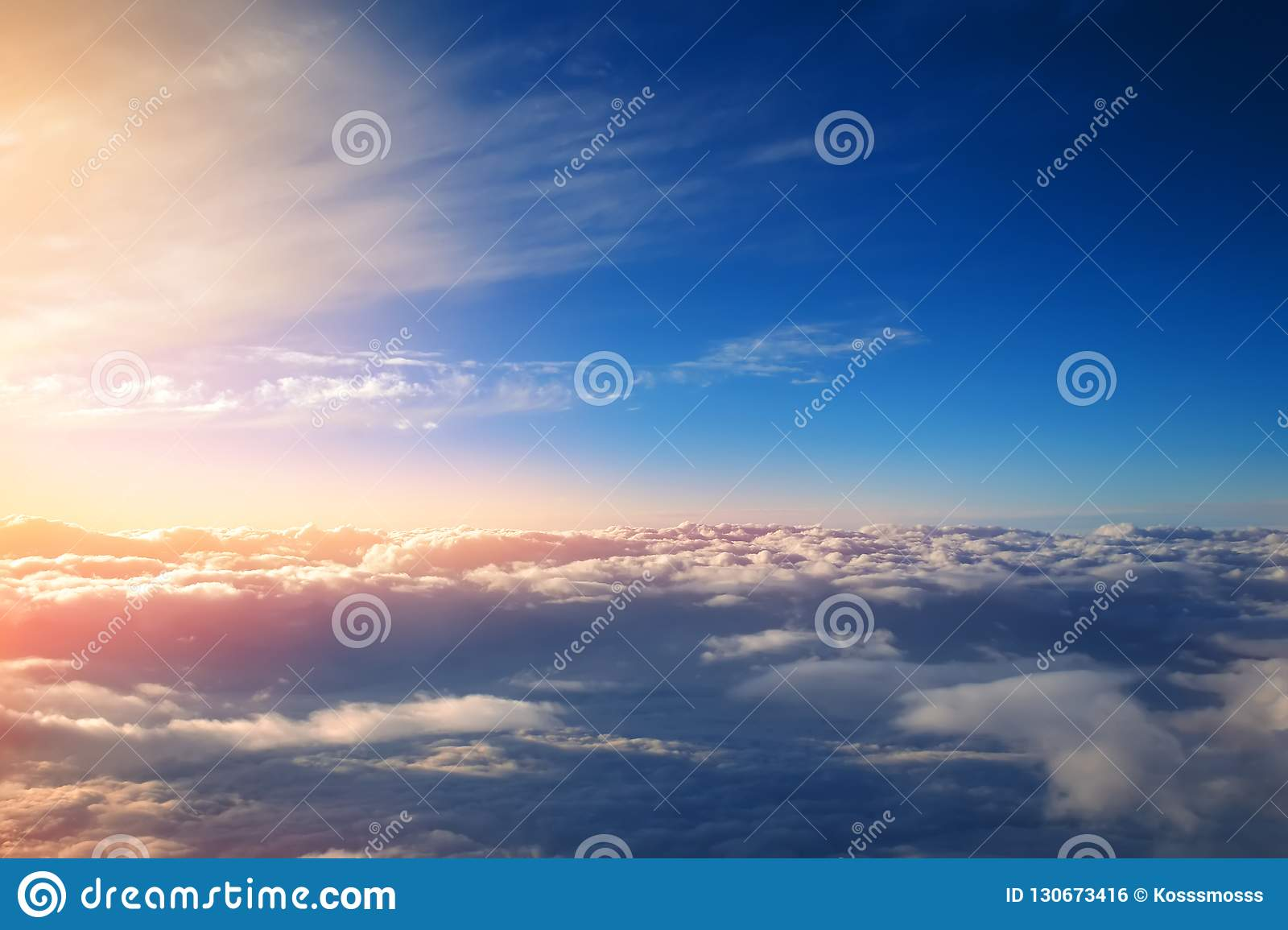 Sunset with bright sun rays over cumulus clouds view from the window of an airplane