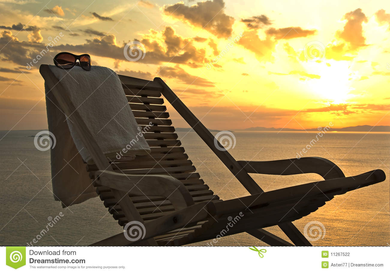 Sunset. chaise lounge with a towel and sunglasses
