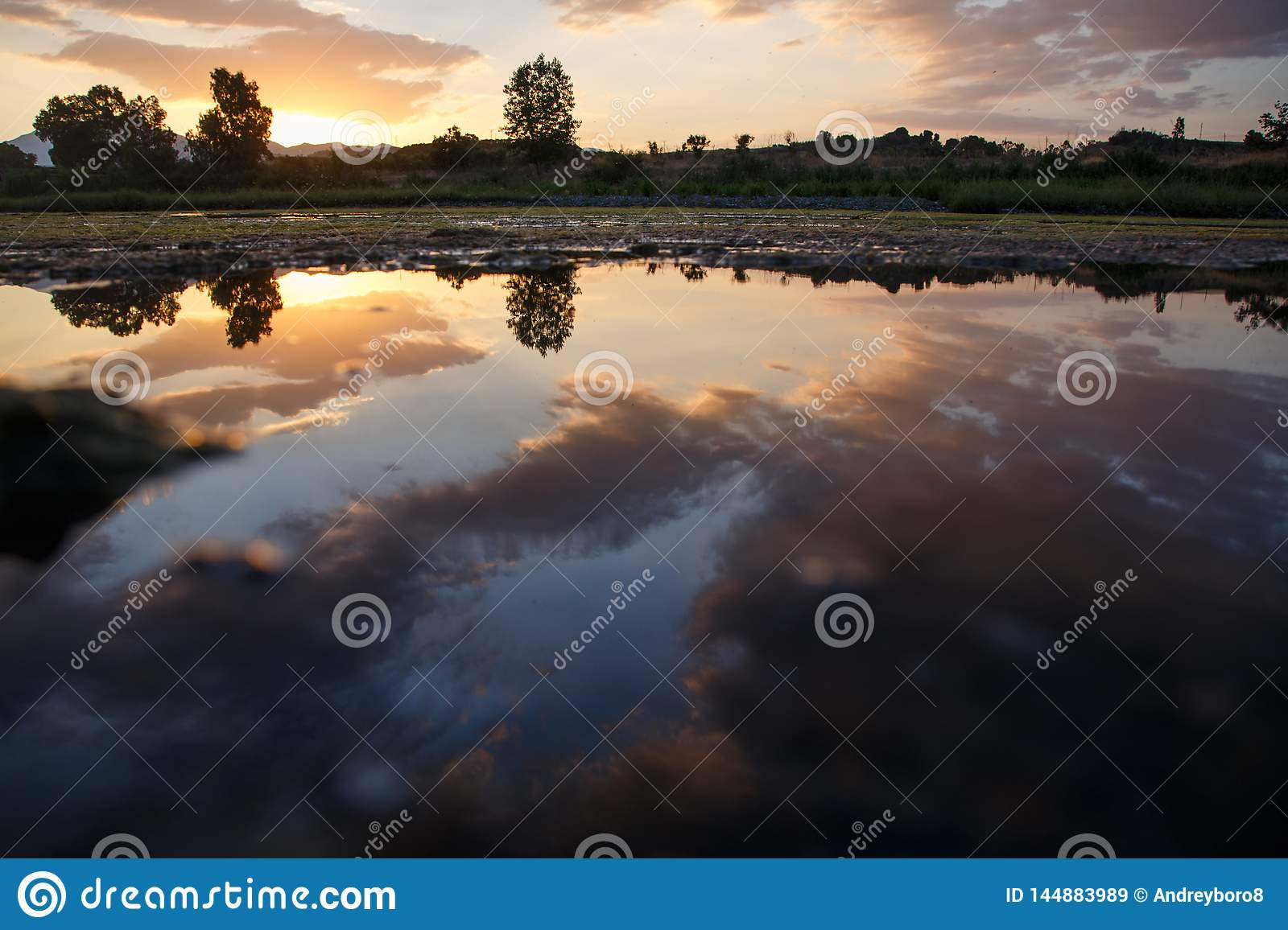 Sunset with clouds reflected on the water of a lake