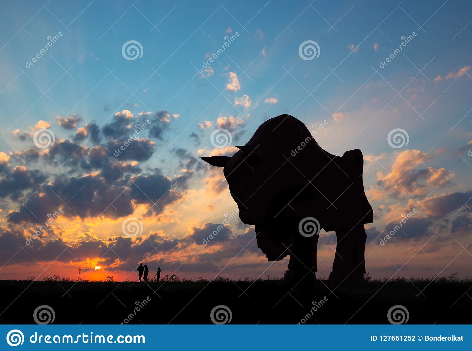 Sunset dawn sun rays over the city sky field statue bison sculpture silhouette family walking near the sun