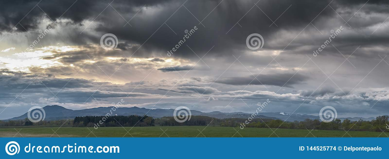 Sunset on a dramatic clouds sky over a meadow and small pine forest with hills in background, near Zagreb