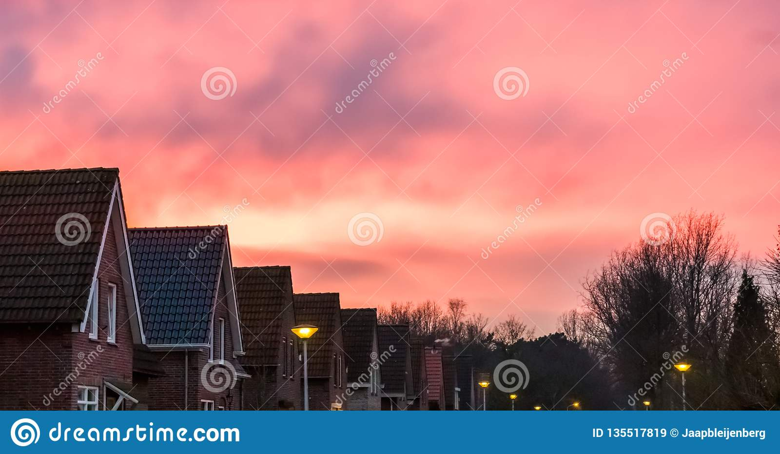 Sunset in a dutch neighborhood, pink nacreous clouds in the sky, a rare weather phenomenon
