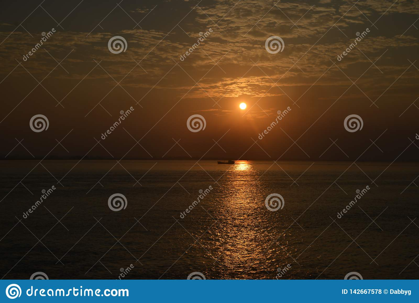 Sunset in India with a boat crossing the suns rays.