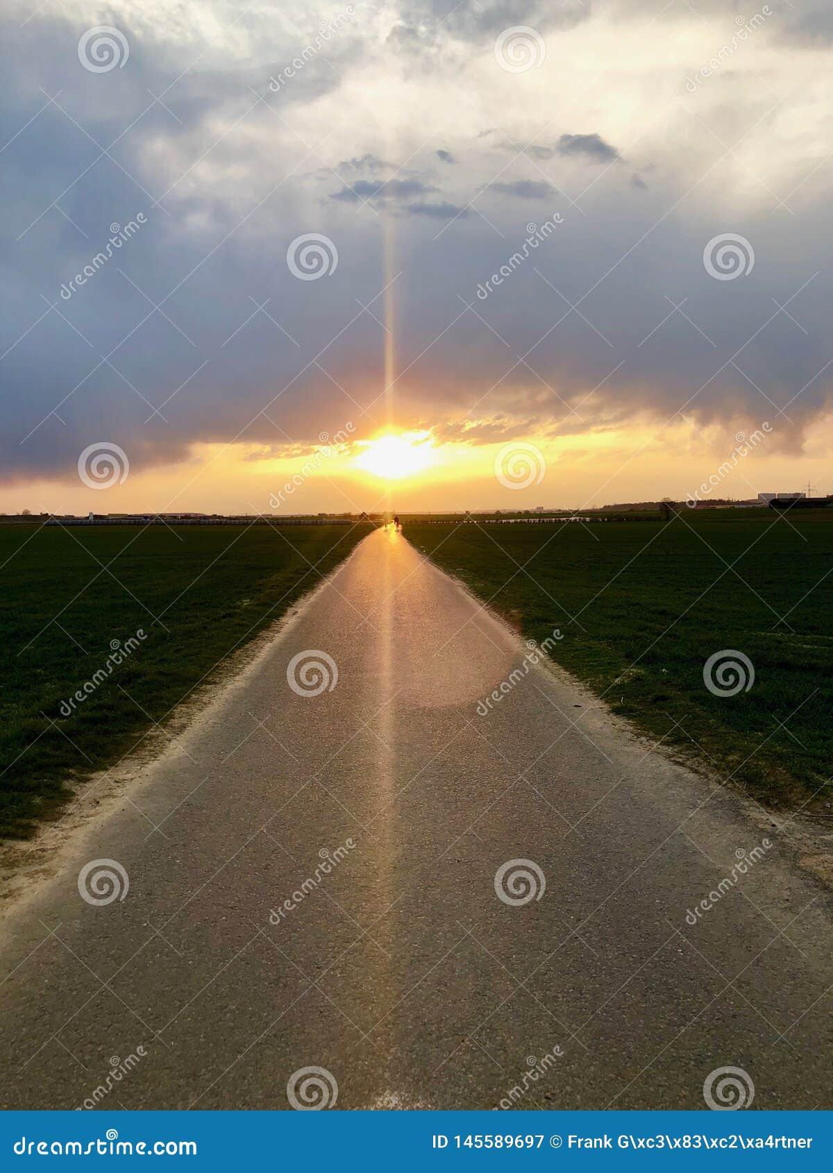 Sunset light above asphalt road