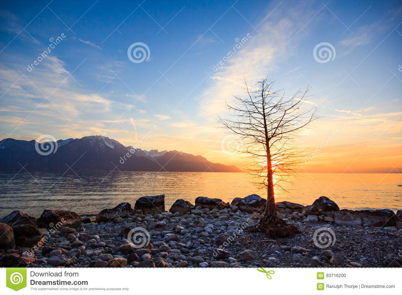Sunset Over A Mountains Range Reflecting In A Lake Stock Photo