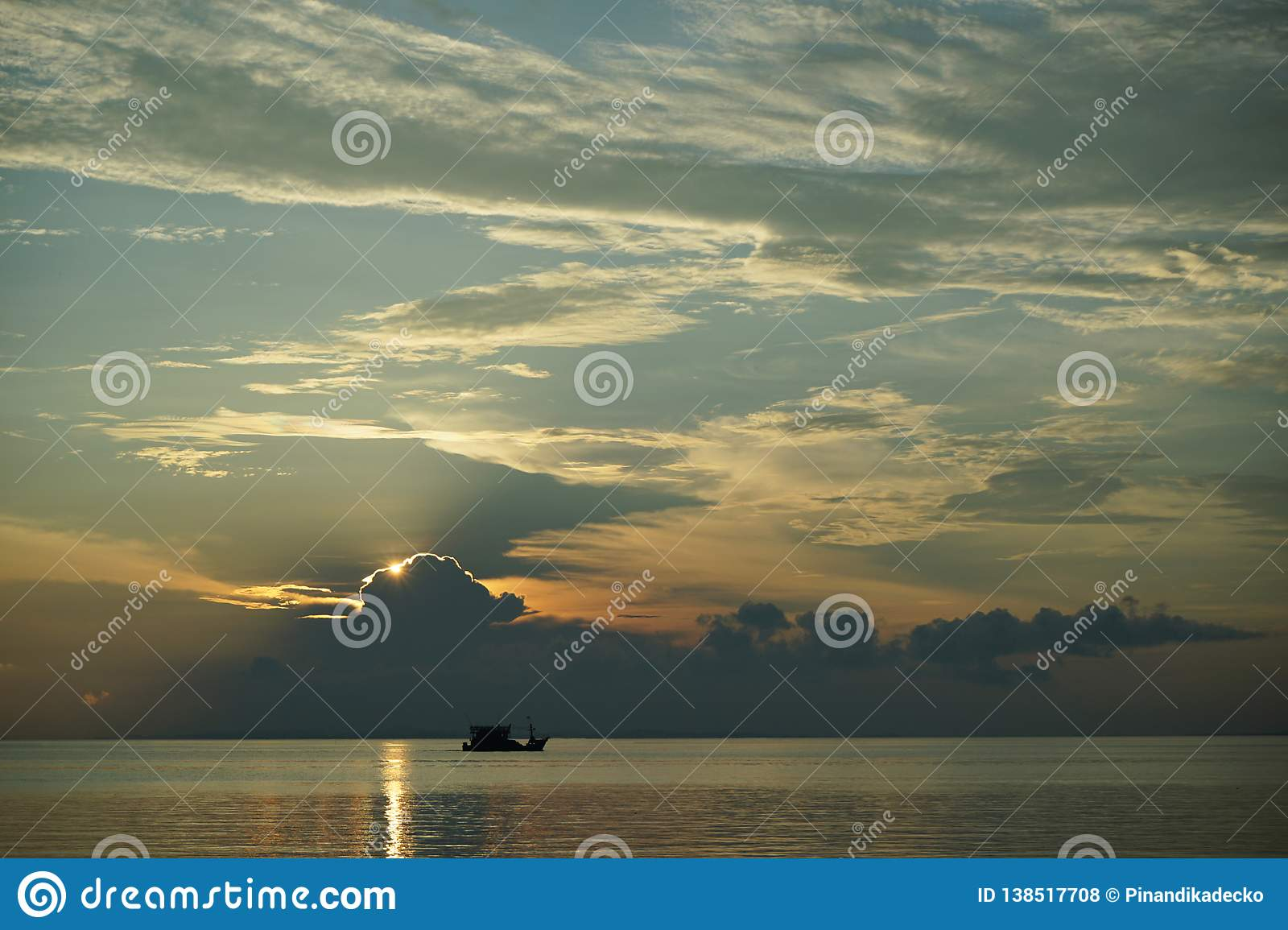 Boat at Sunset and sunrise with dramatic sky over ocean