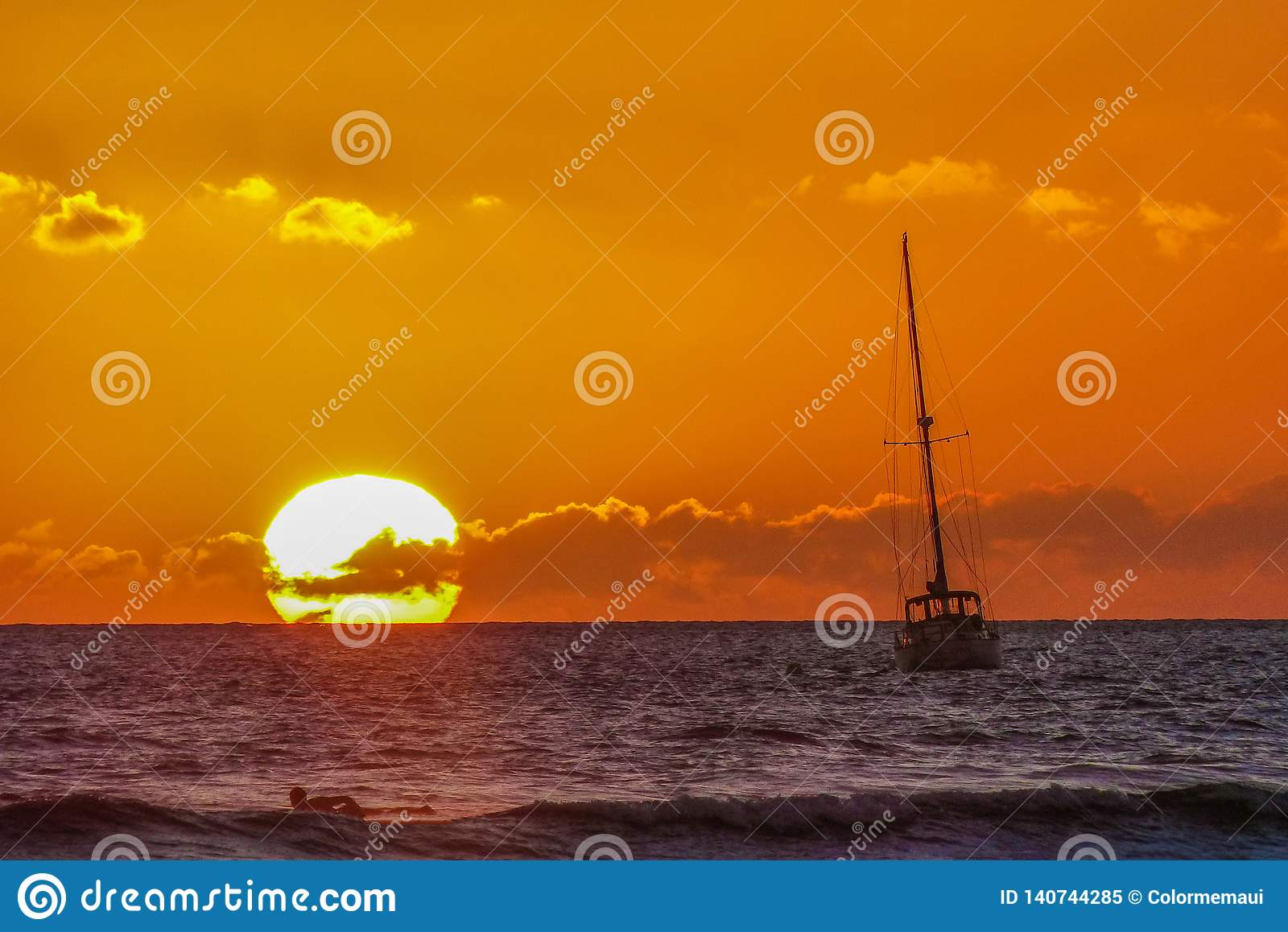 Sunset Over the Ocean with Sail Boat and Surfer in Maui HawaiiSunset
