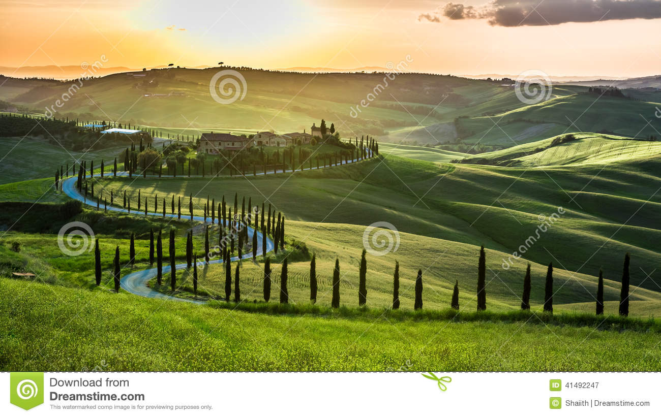 Sunset over the winding road with cypresses in Tuscany