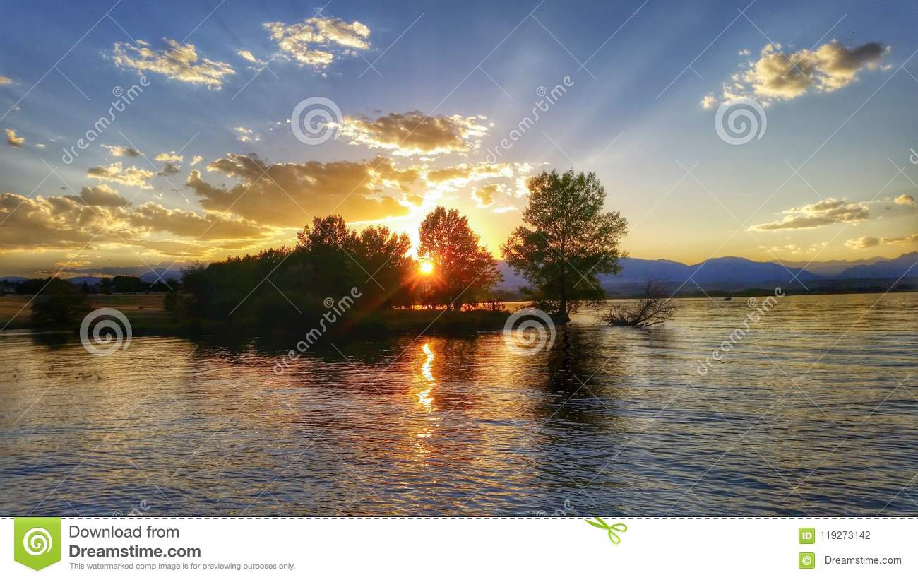 Sunset rays through trees on the lake