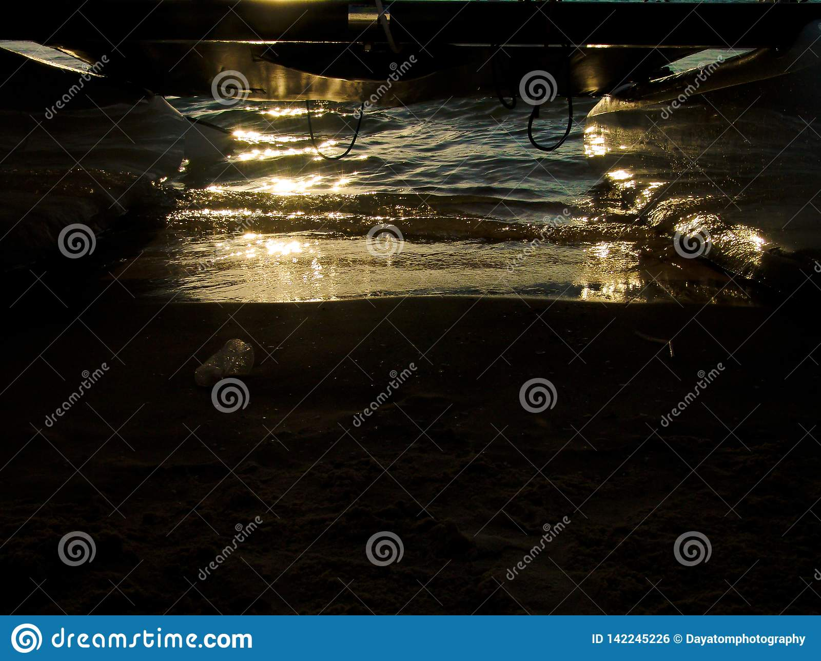 Sunset reflection on wet sand over a sandy beach in the ocean, under a wind surf board boat