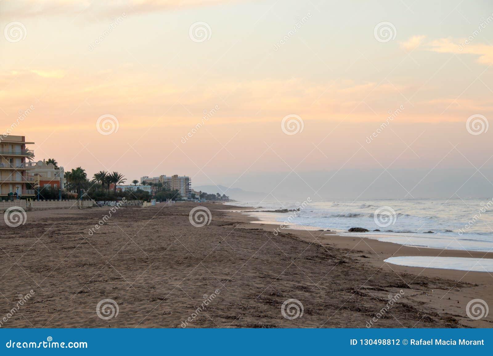 Sunset on a sandy beach after summer