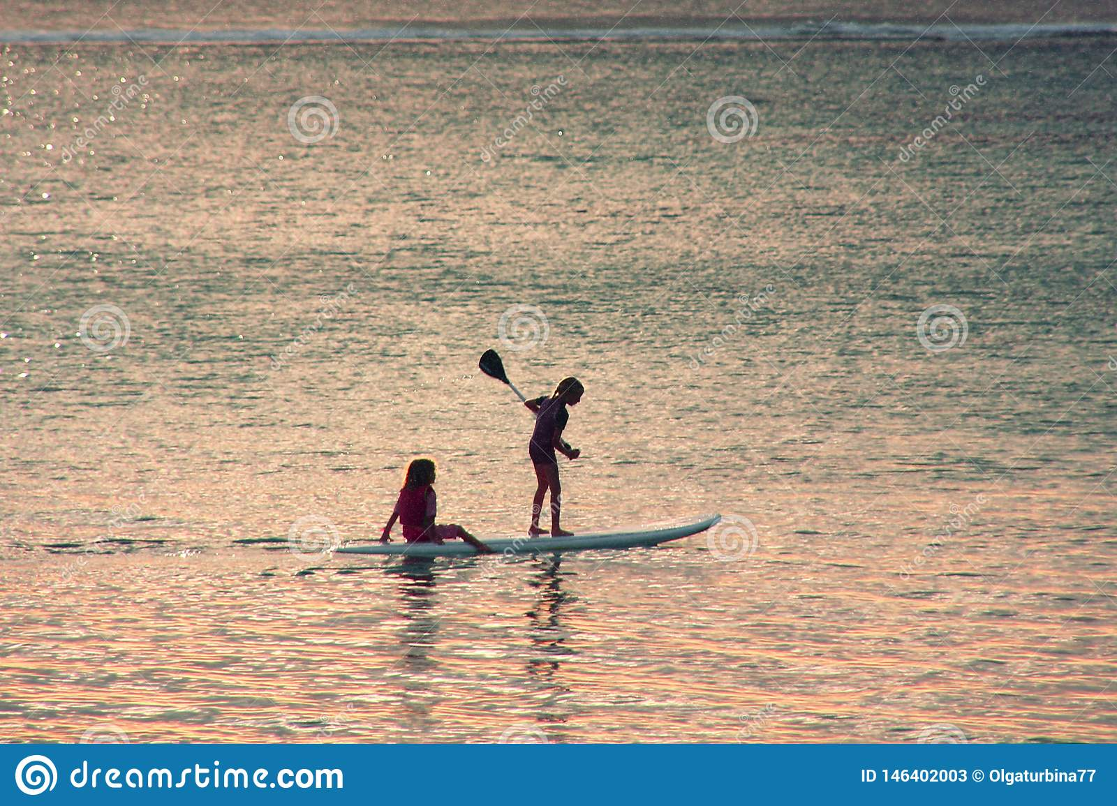 Sunset scene on background. Two little girls silhouettes are padddling