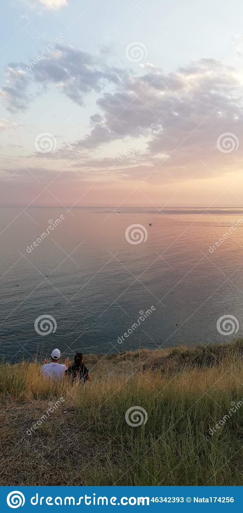 Sunset seascape. Loving couple by the sea