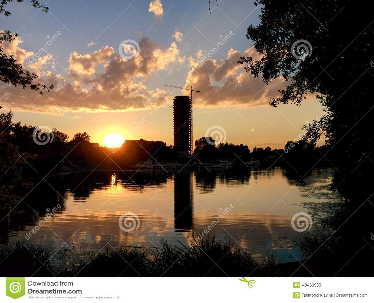 Sunset and silhouette of town with reflection in water