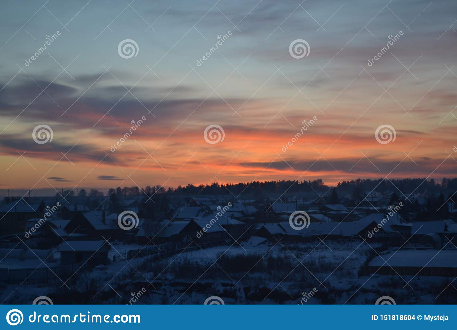 Sunset on the sky over the winter Russian village