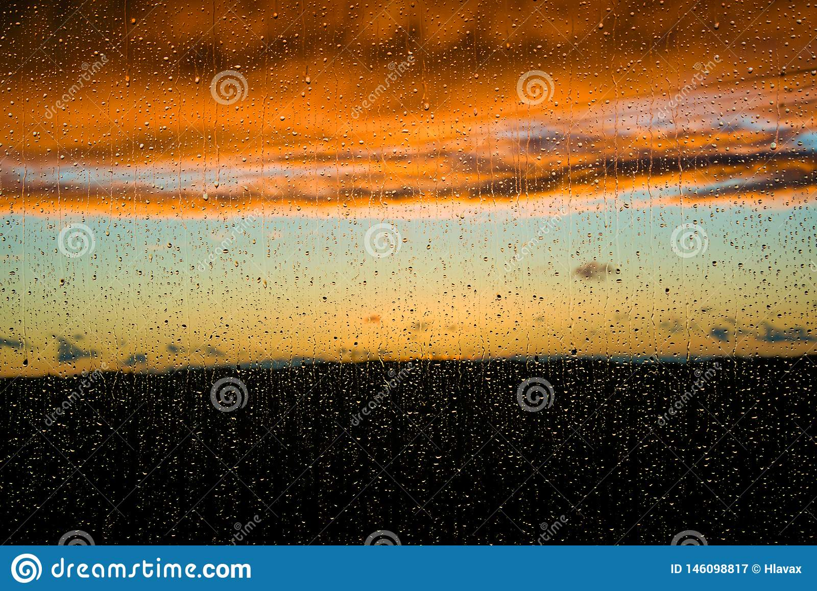 Sunset under the rain through the window