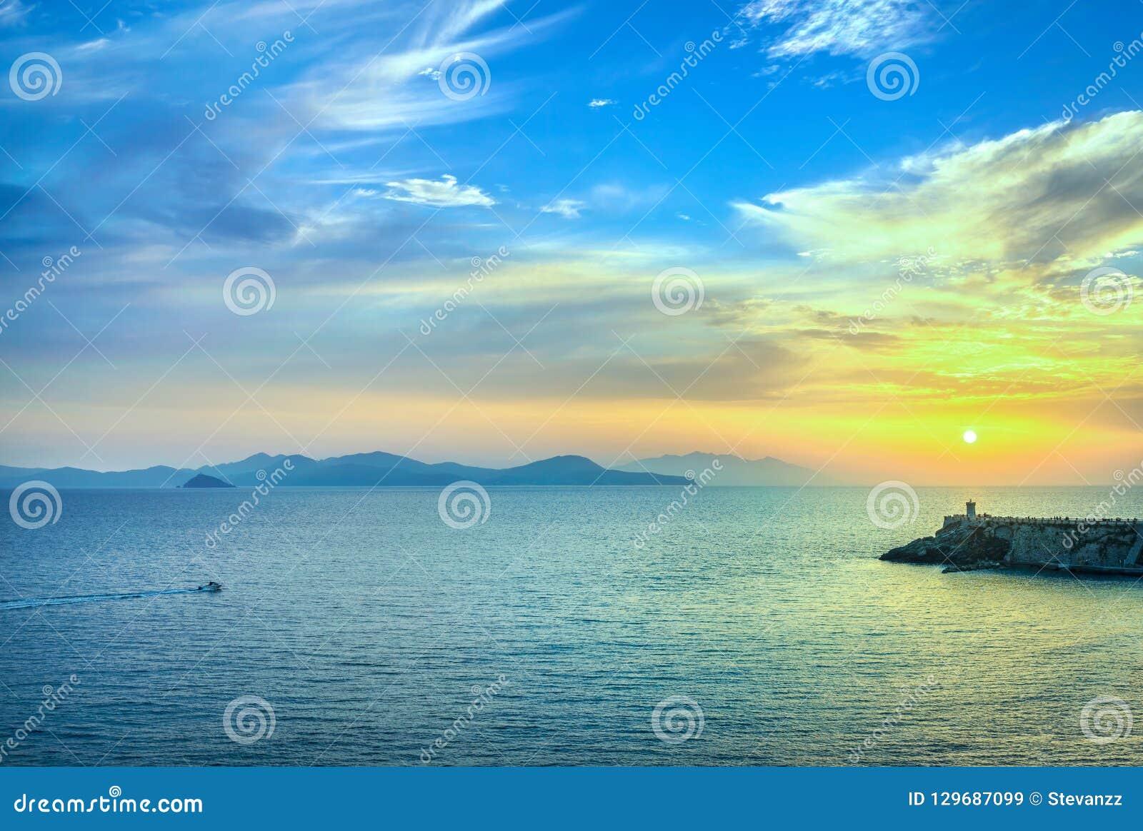 Sunset view of Elba Island and Piombino piazza bovio lighthouse.