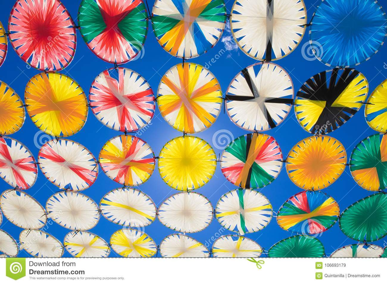 Sunshade multicolored circles row in blue sky horizontal