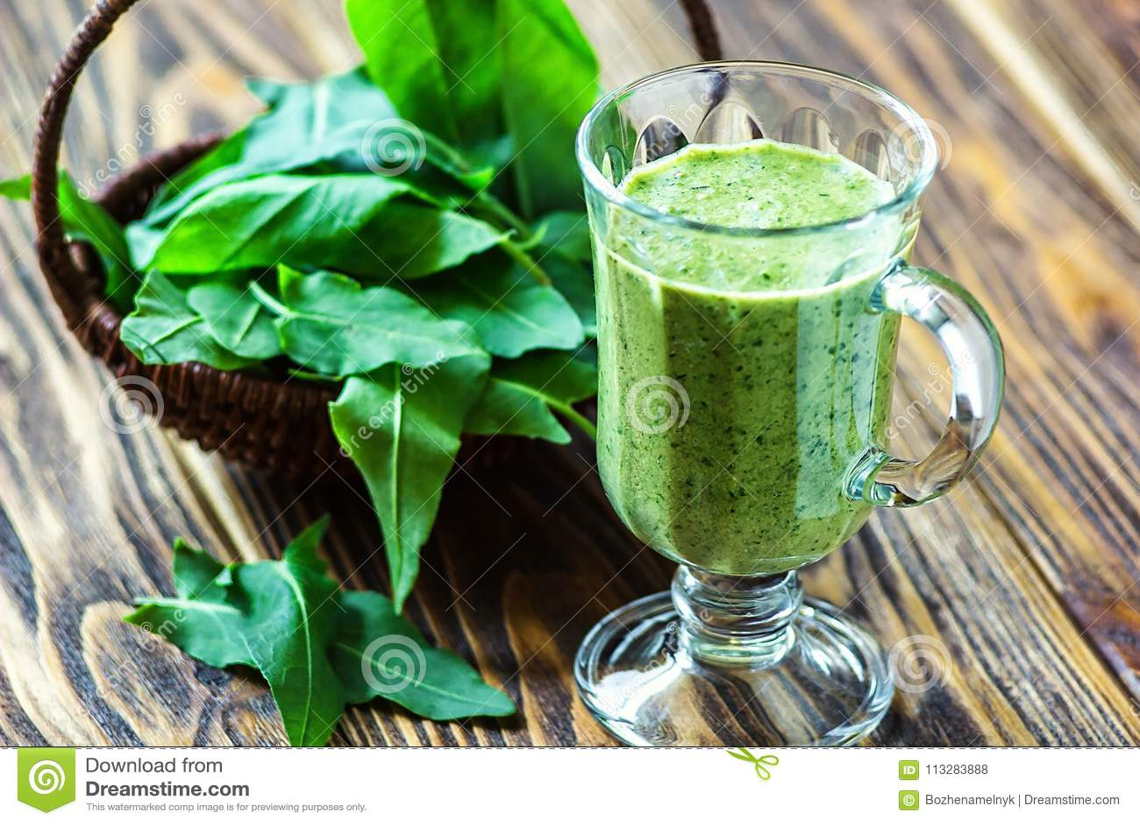 Sunt äta, drinkar och bantar begrepp Den härliga aptitretaregräsplansmoothien eller spenatfruktsaft i den glass kruset med nya si