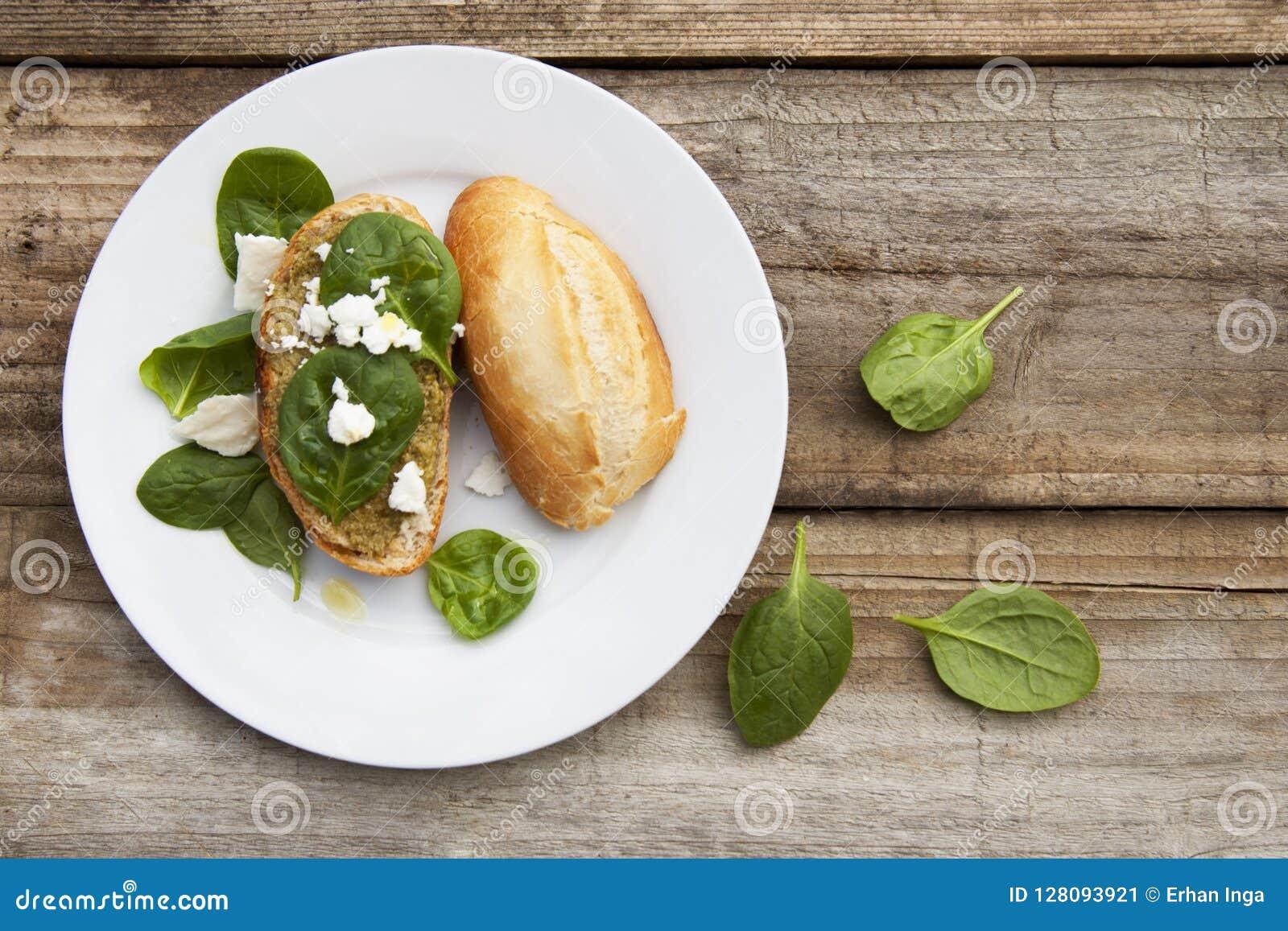 Sunt mellanmål Bulle eller bröd med pestopasta- och basilikasidor Lantlig trätabell, bästa sikt