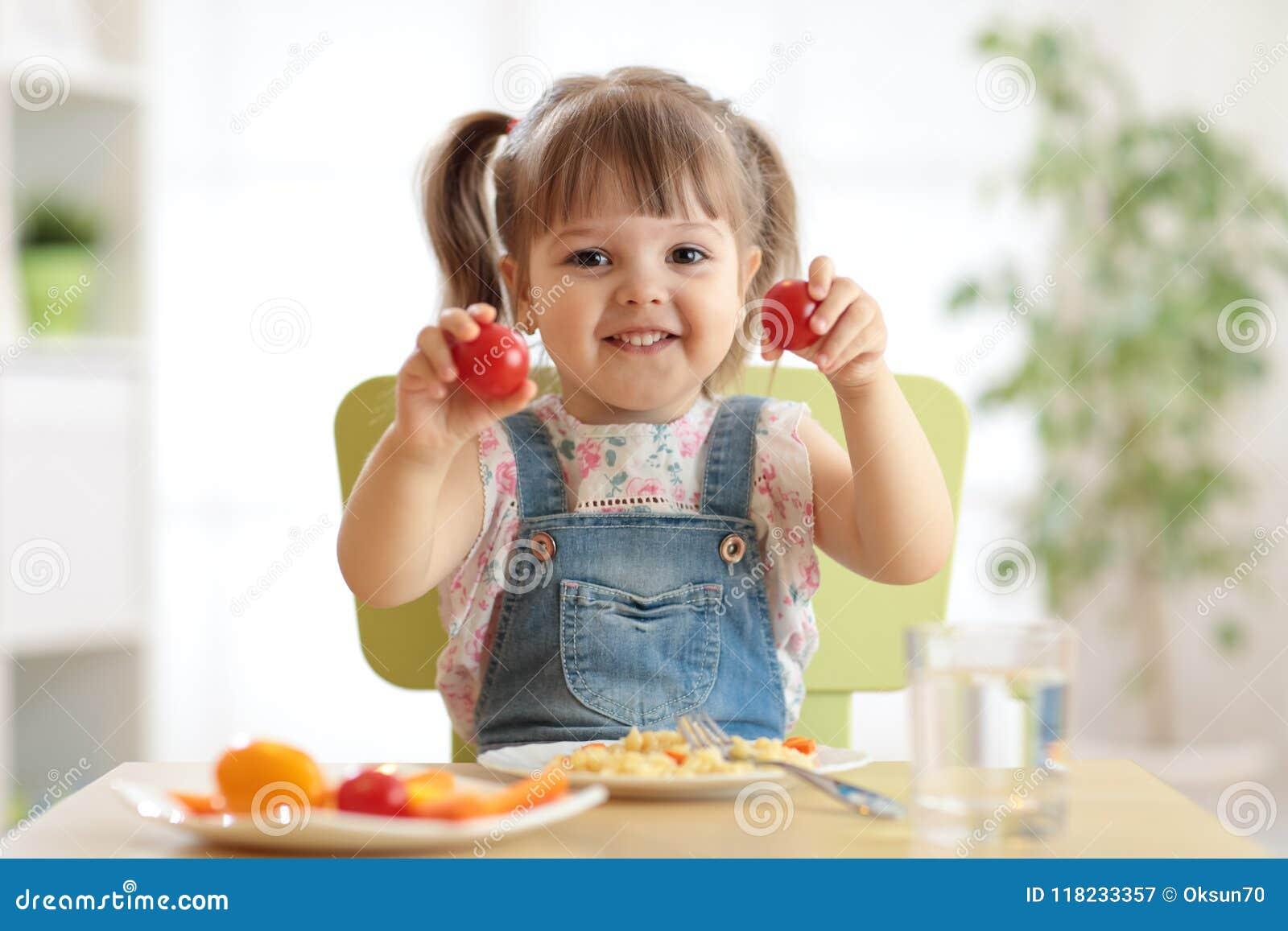 Sunt ungenäringbegrepp Gladlynt litet barnflickasammanträde på tabellen med plattan av sallad, grönsaker, pasta i rum
