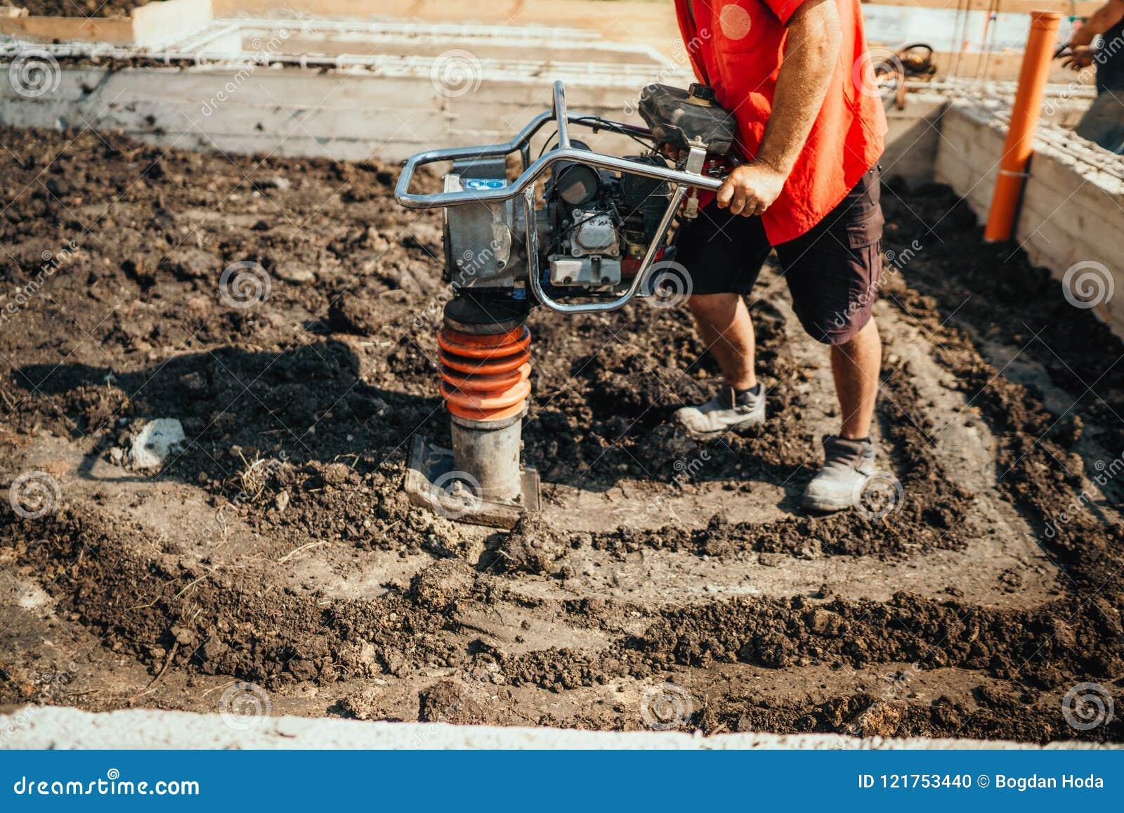 Suolo comprimente del lavoratore dell industria nel fondamento della casa facendo uso del compattatore