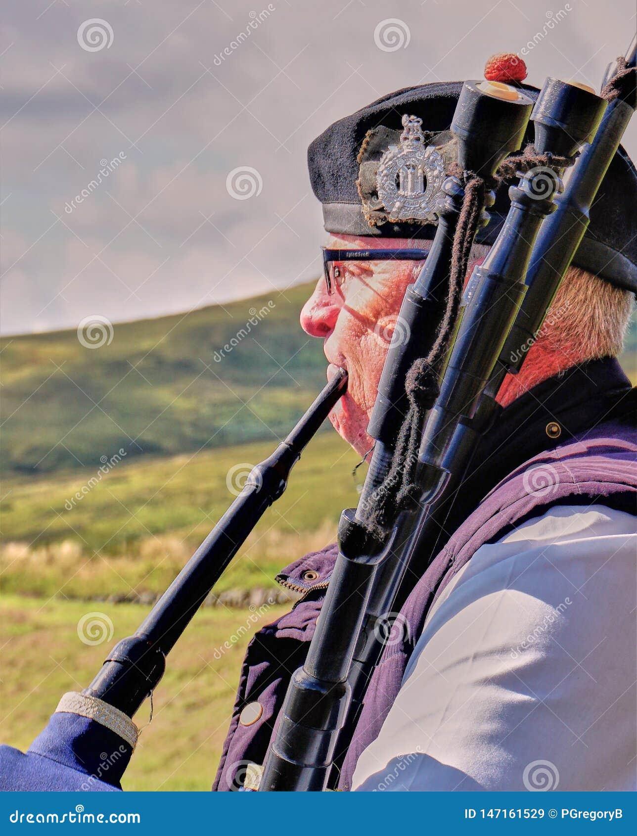Suonatore di cornamusa & altopiani scozzesi - chiuda su
