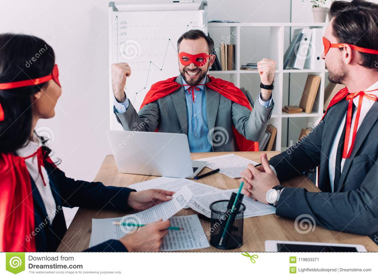 super businessman showing yes gesture to colleagues