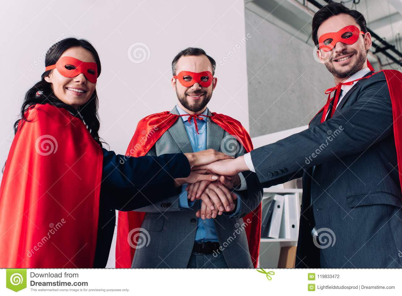 super businesspeople in masks and capes putting hands together