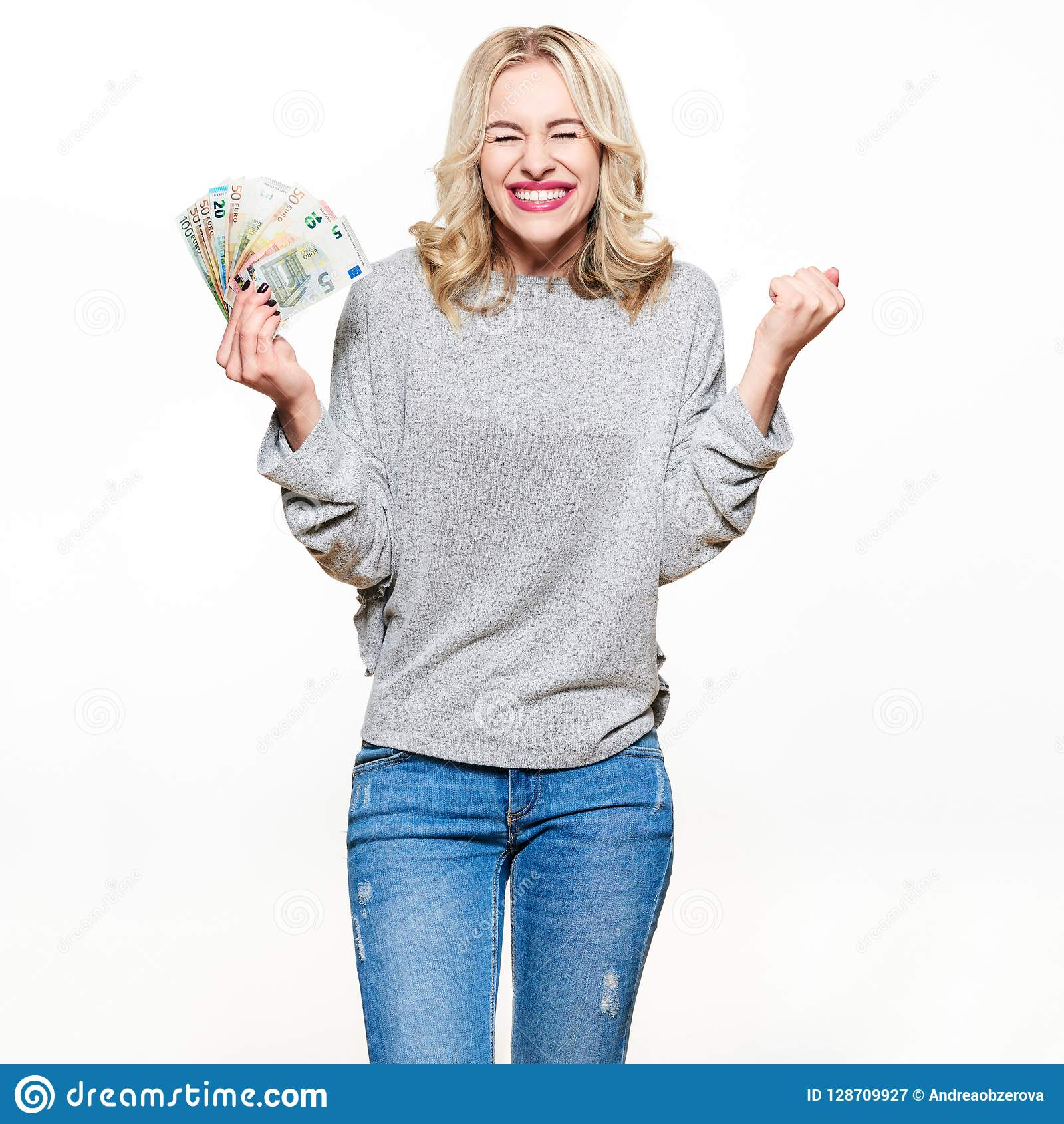 Super excited young woman in grey sweater and jeans holding bunch of Euro banknotes, clinching fists, celebrating.