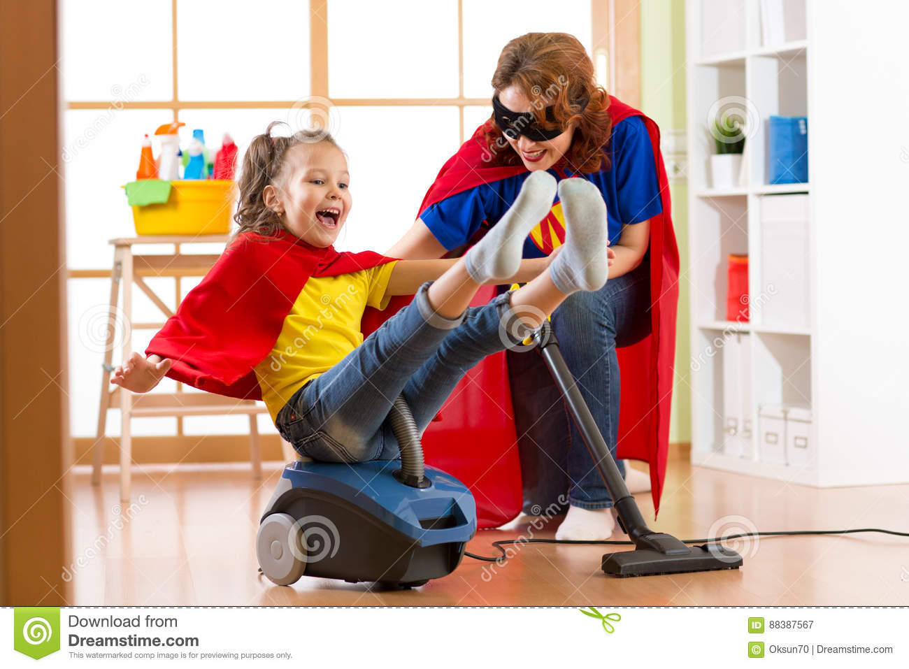 Super hero kid flying on vacuum cleaner. Mother and child daughter cleaning the room and have a fun