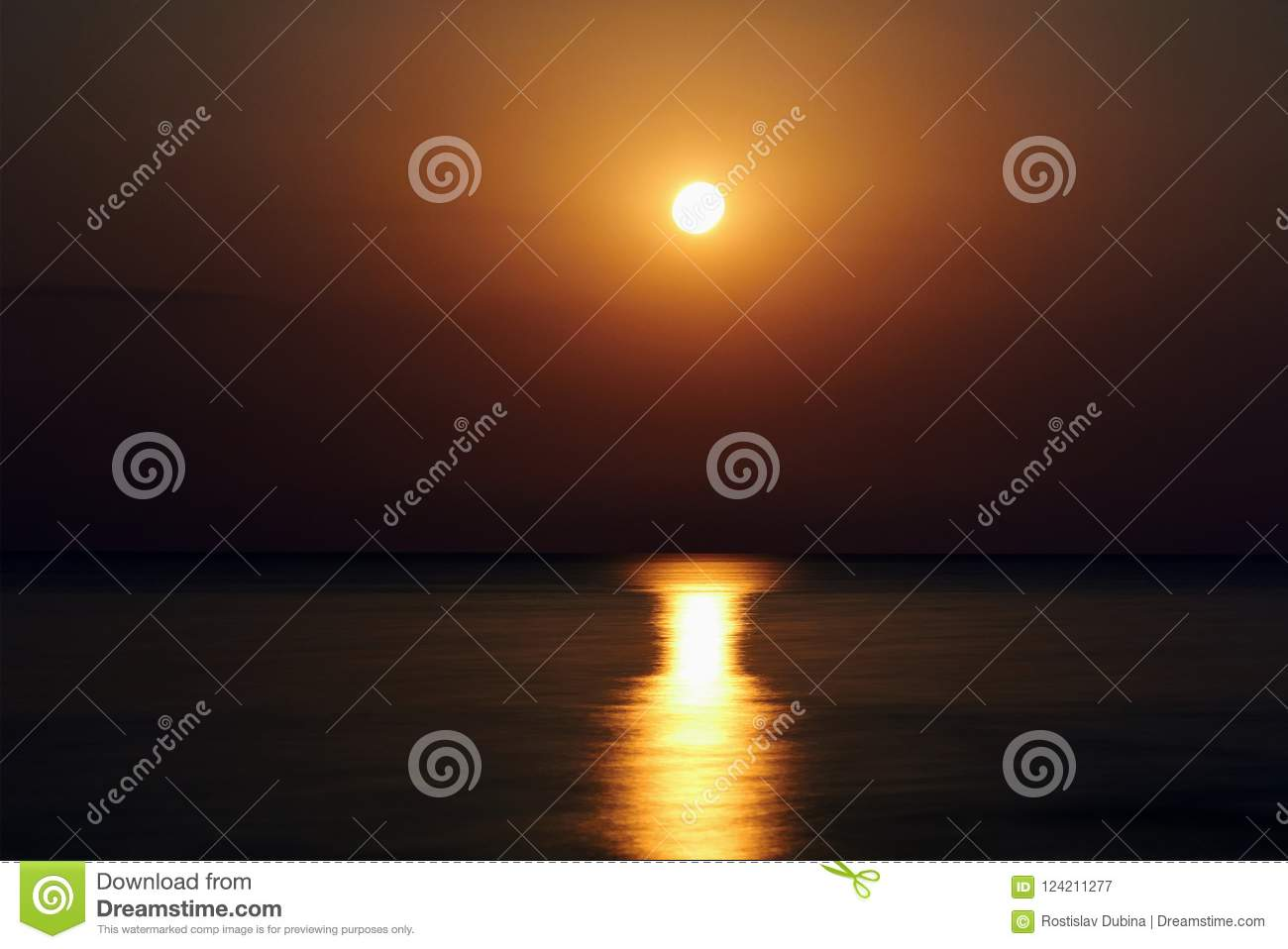 The super moon on the beach. The moon track is reflected in the water. The night moon came up over the water. Full moon on the bea