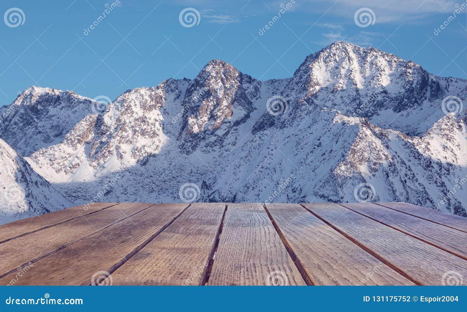 Superficie vuota della tavola contro la cima di una montagna nevosa Viaggio e vacanza di concetto nelle montagne nell inverno