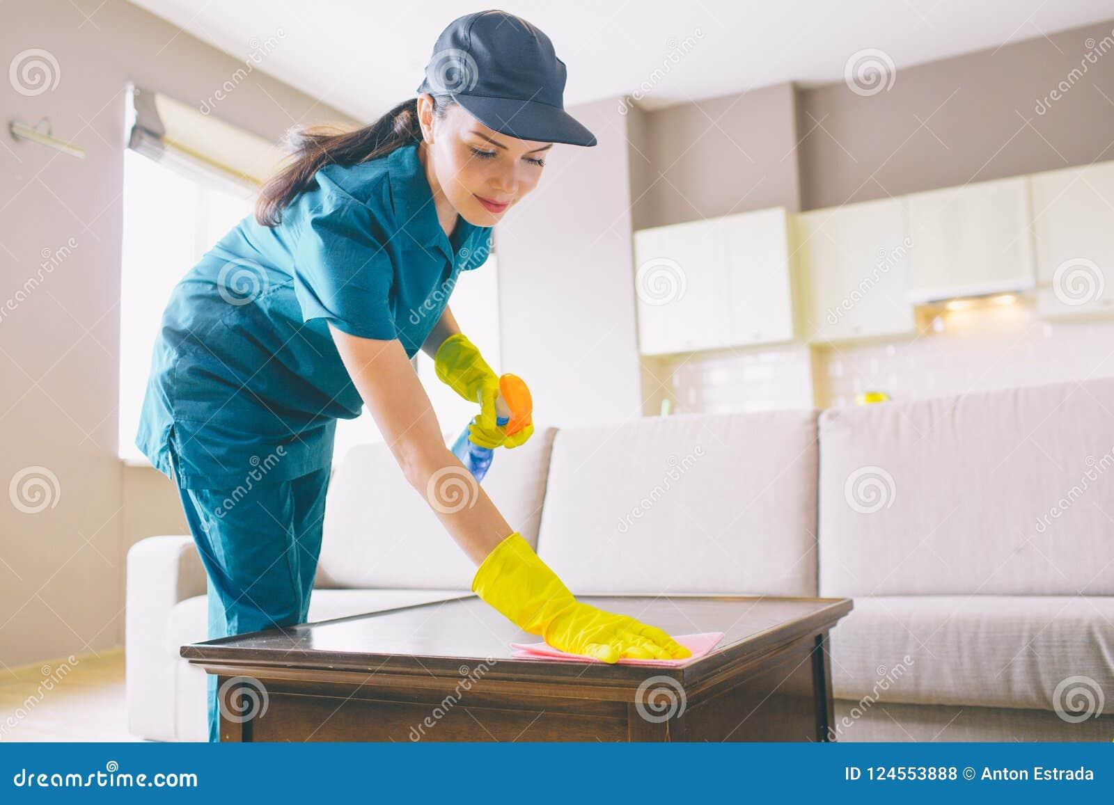 Superficie wahsing del pulitore professionale della tavola usa lo straccio e lo spruzzo La ragazza lo fa attento