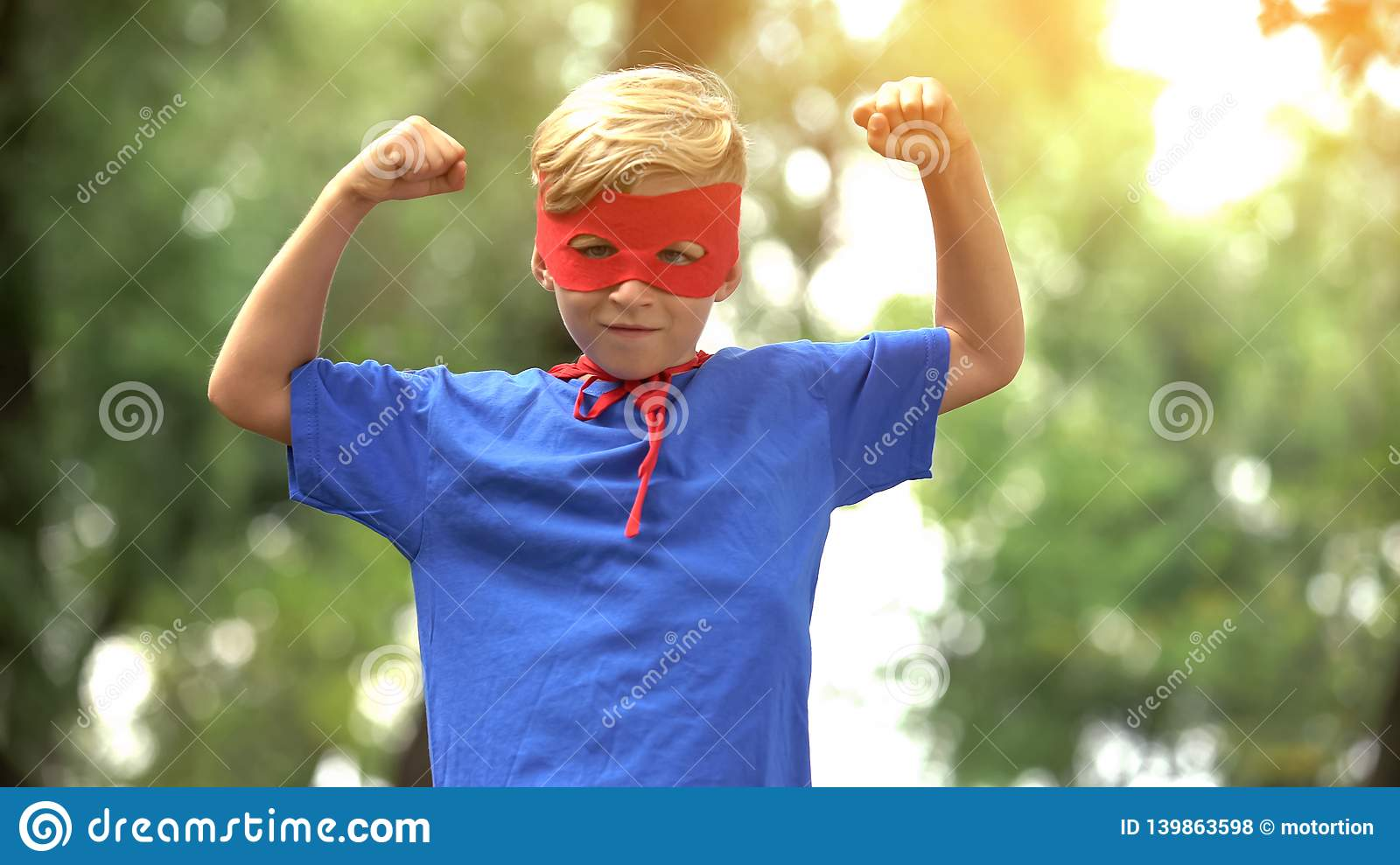 Superhero boy showing muscles, game as psychotherapy for child confidence