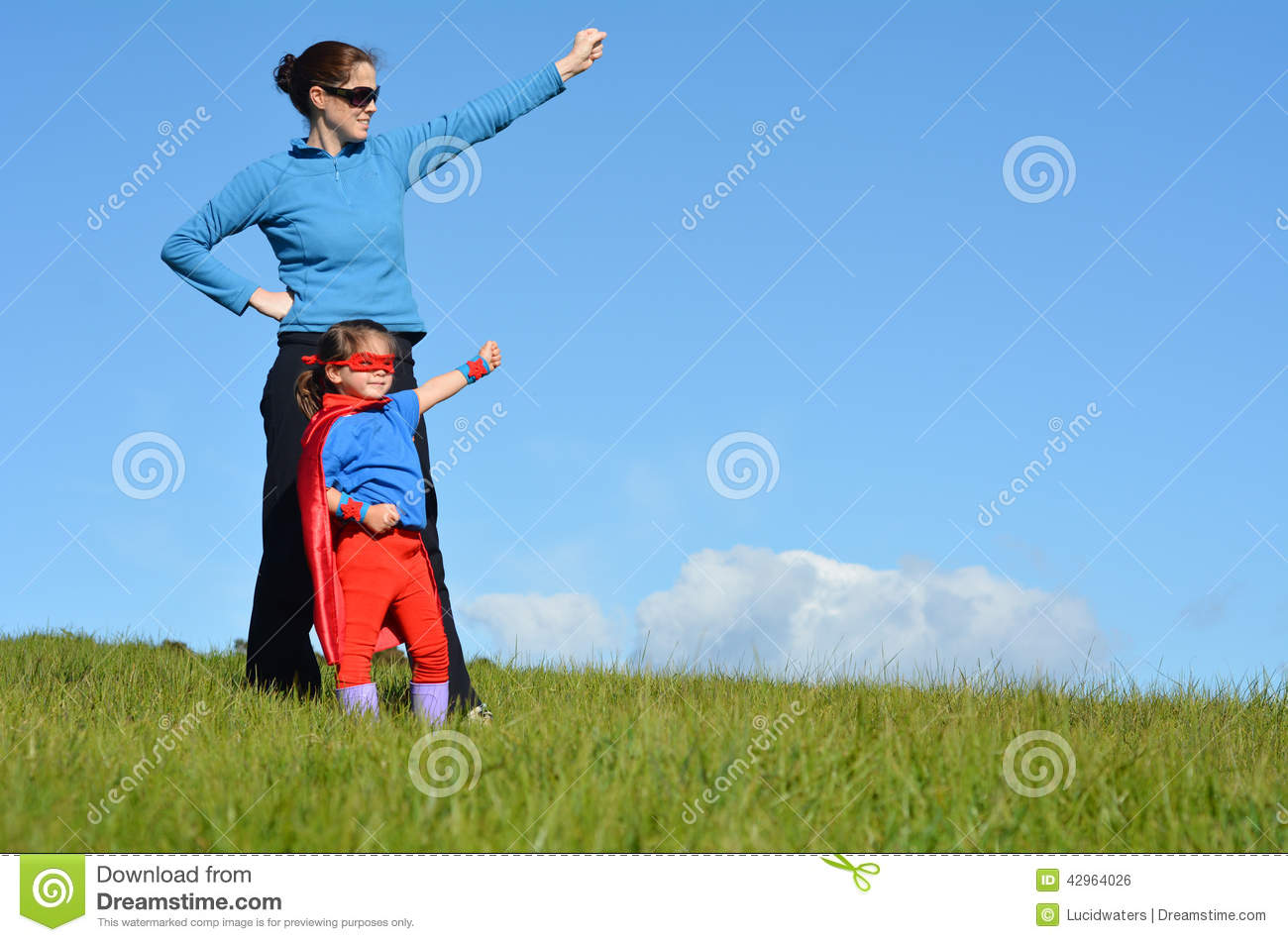 Superhero mother and daughter against dramatic blue sky background ...