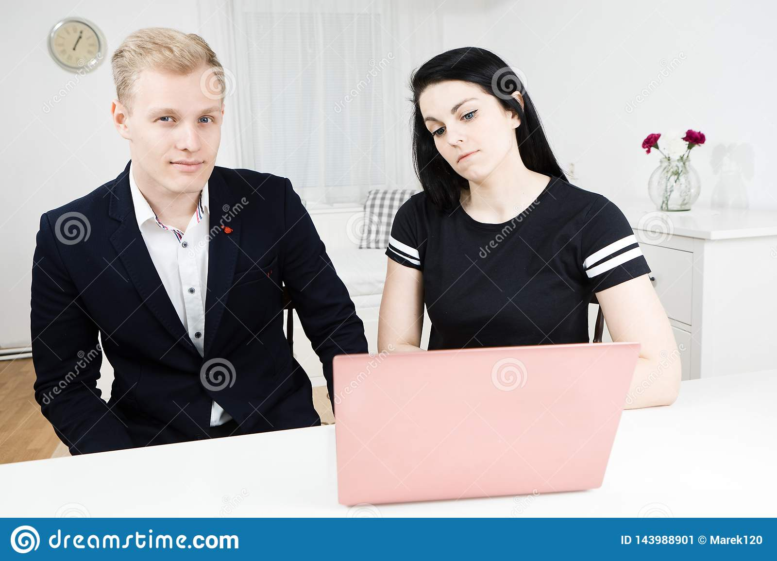Superiors works with subordinate. Blond man working with black haired woman
