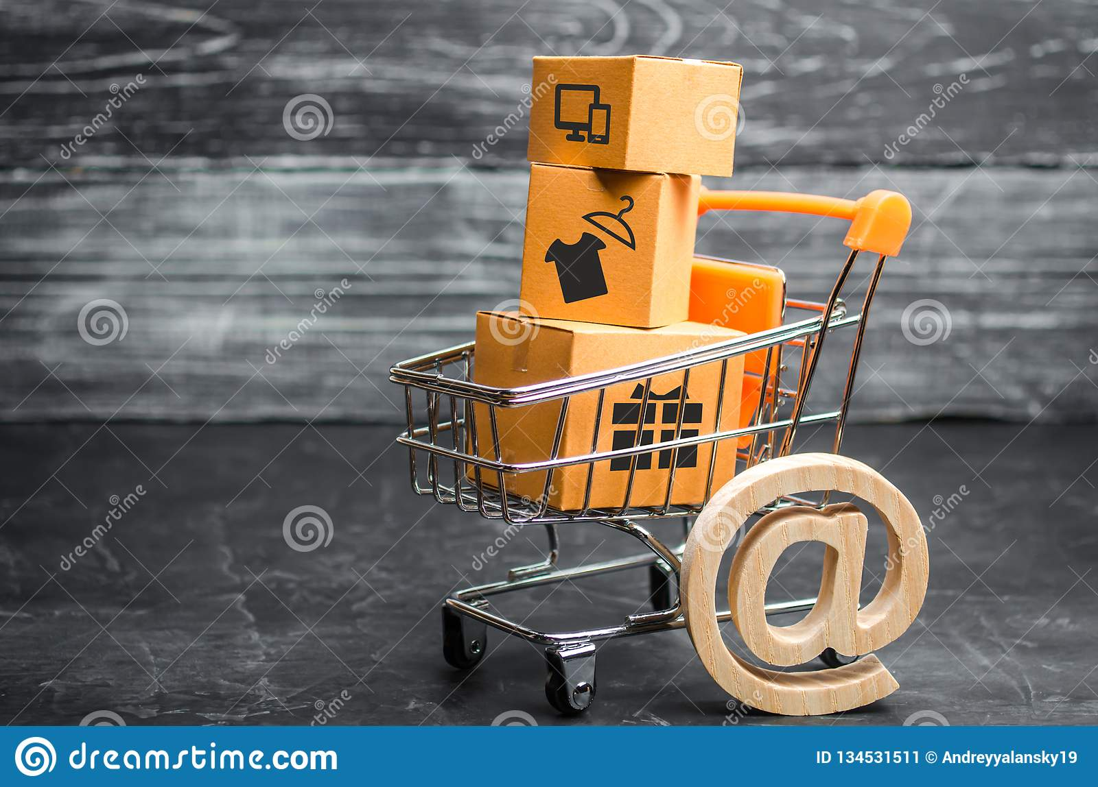 Supermarket cart with boxes, merchandise: the concept of buying and selling goods and services, internet commerce, online shopping