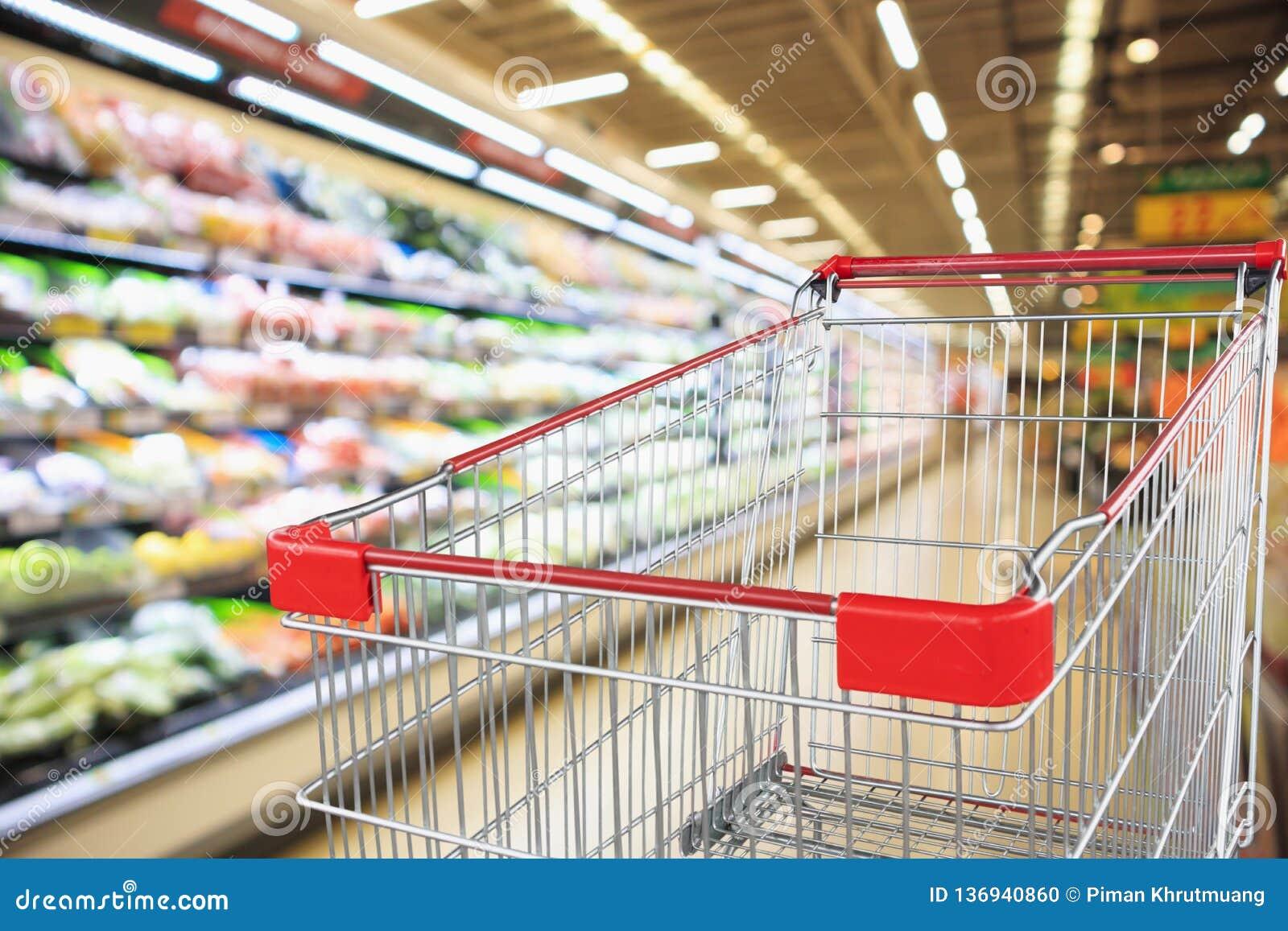 Supermarketlivsmedelsbutik med inre defocused bakgrund för frukt- och grönsakhyllor med den tomma shoppa vagnen