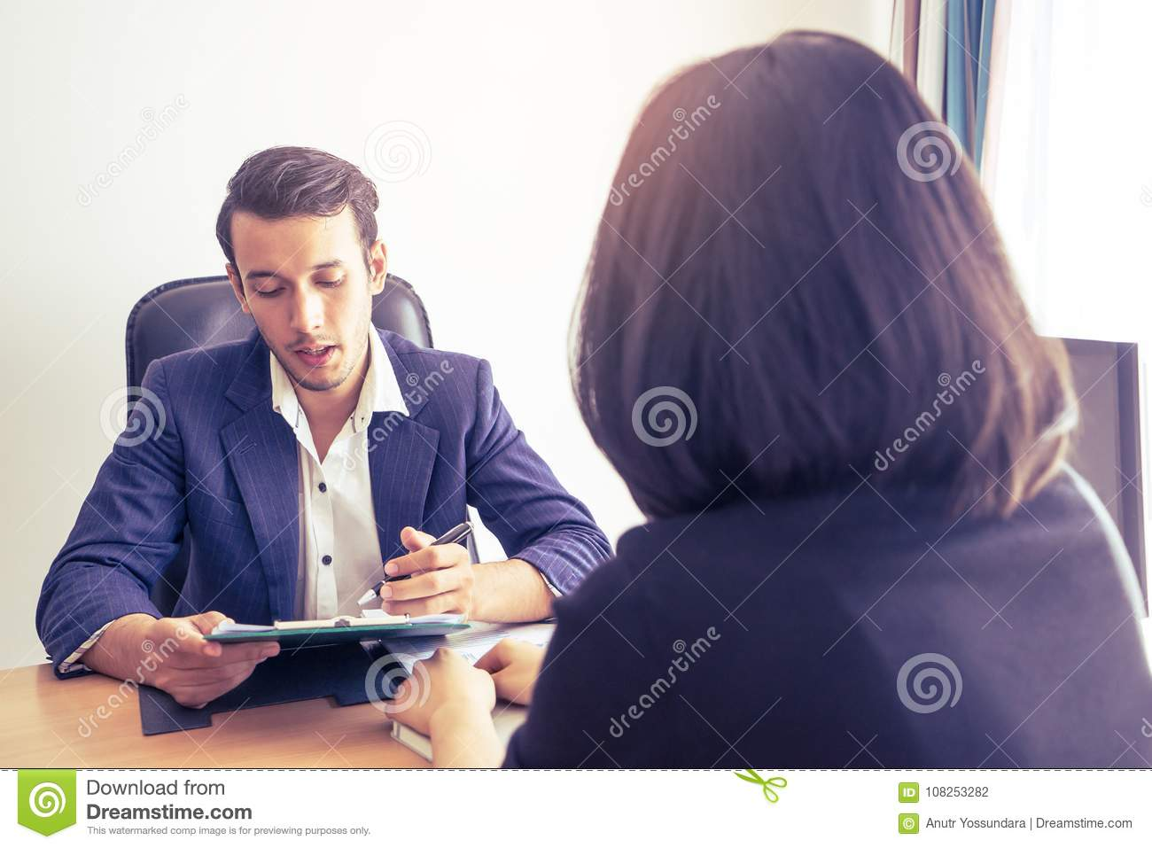 Supervisor explaining documents contractto a female worker