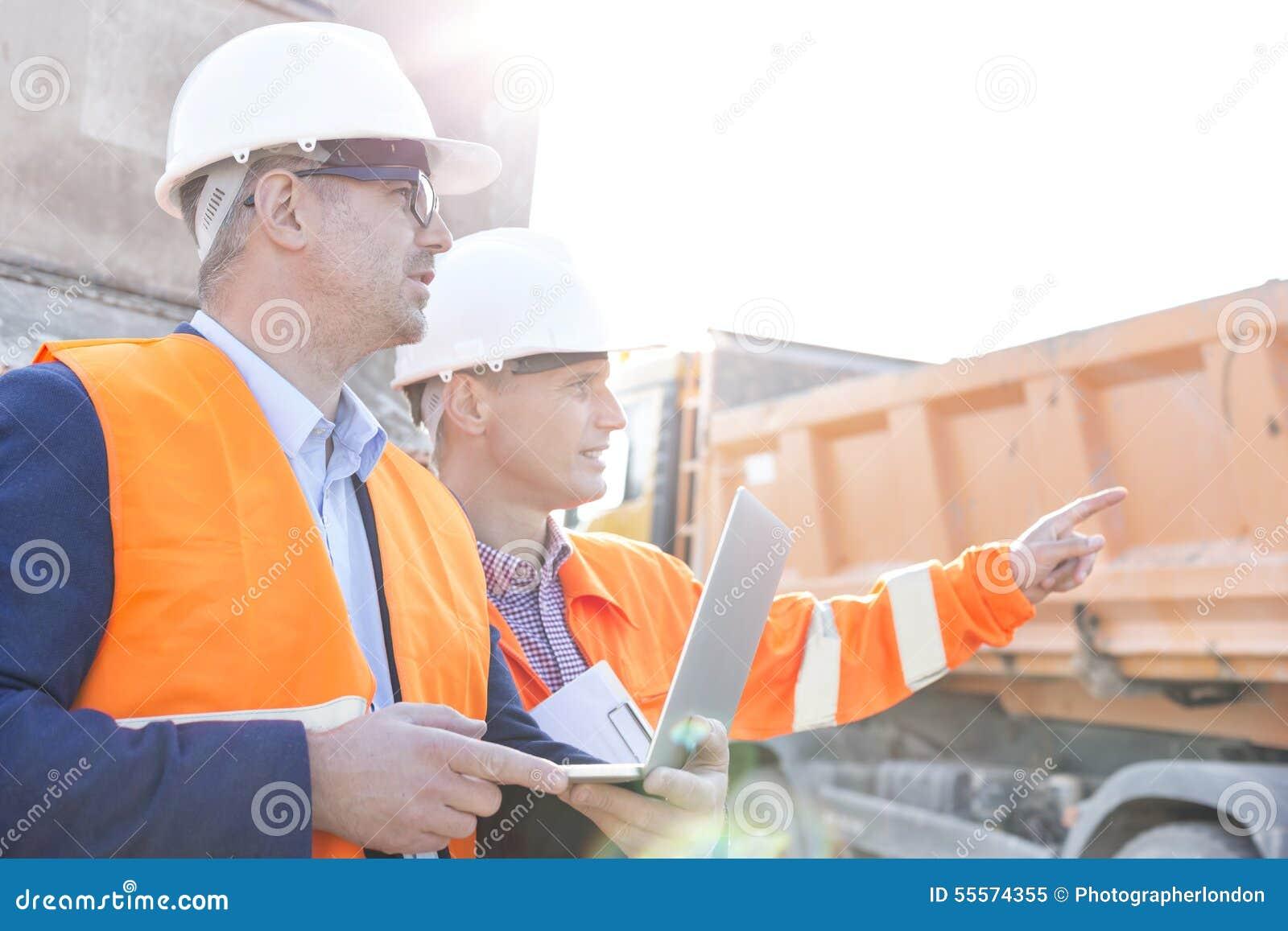 Supervisor que mostra algo ao colega que guarda o portátil no canteiro de obras