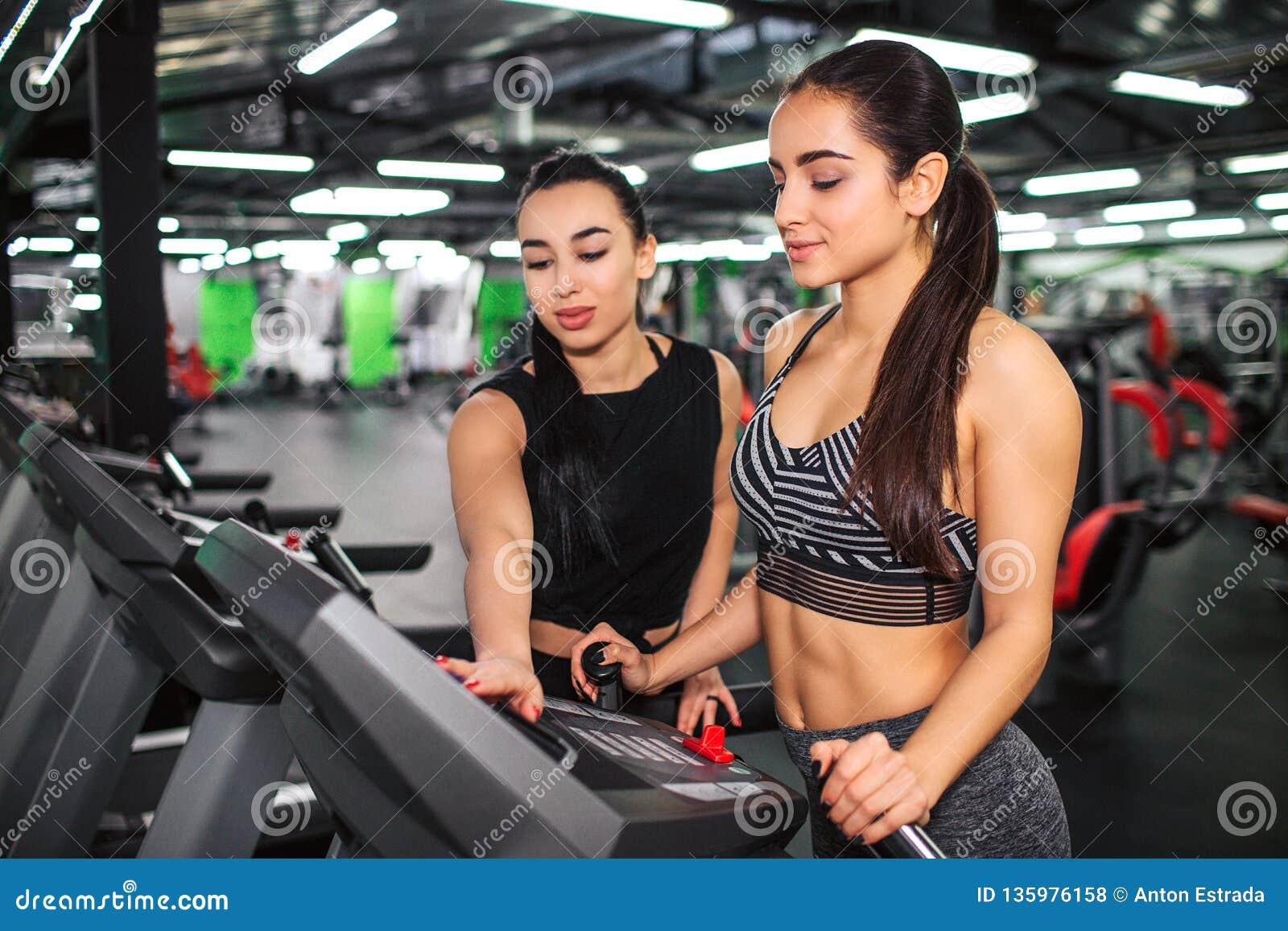 Suporte agradável da jovem mulher na pista de atletismo e olhar em seu painel Ajuda fêmea asiática do instrutor a ajustar ajustes