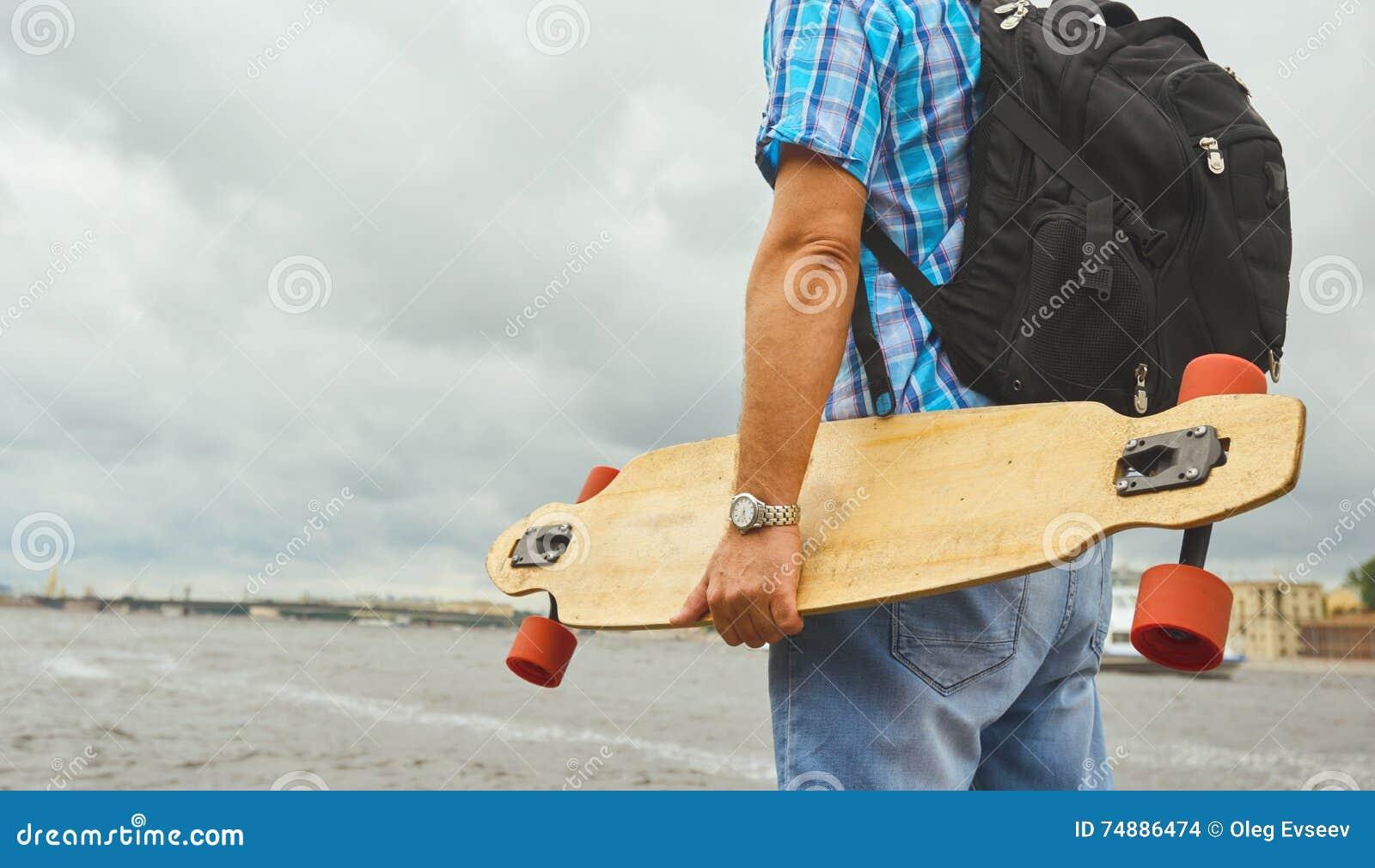 Suporte considerável do indivíduo do moderno com o longboard sobre o fundo do rio da cidade